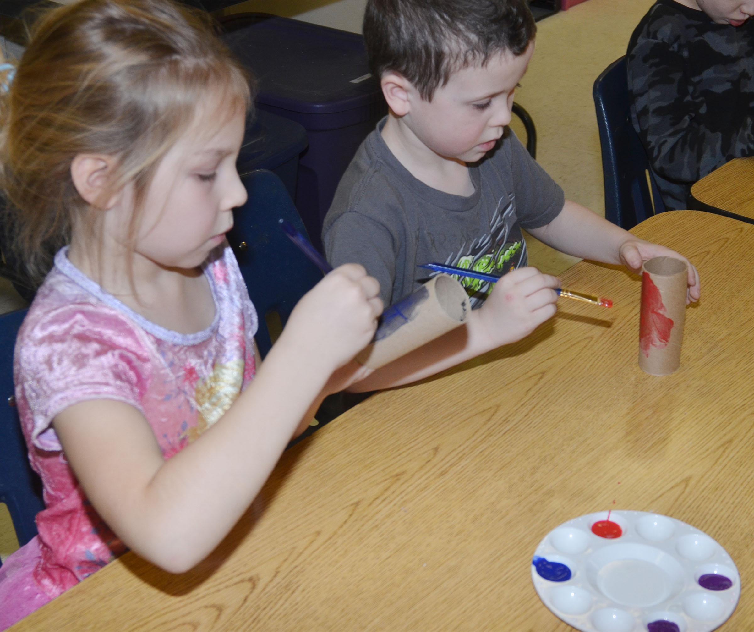 CES kindergarteners Kira Dotson, at left, and Braydan Dyer paint their toilet paper rolls.