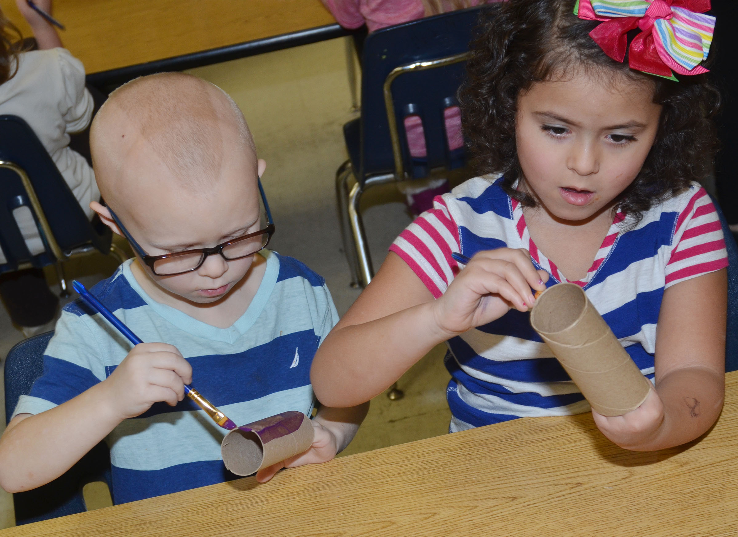 CES kindergarteners Robert Atwood, at left, and Isabella Anderson paint their toilet paper rolls.