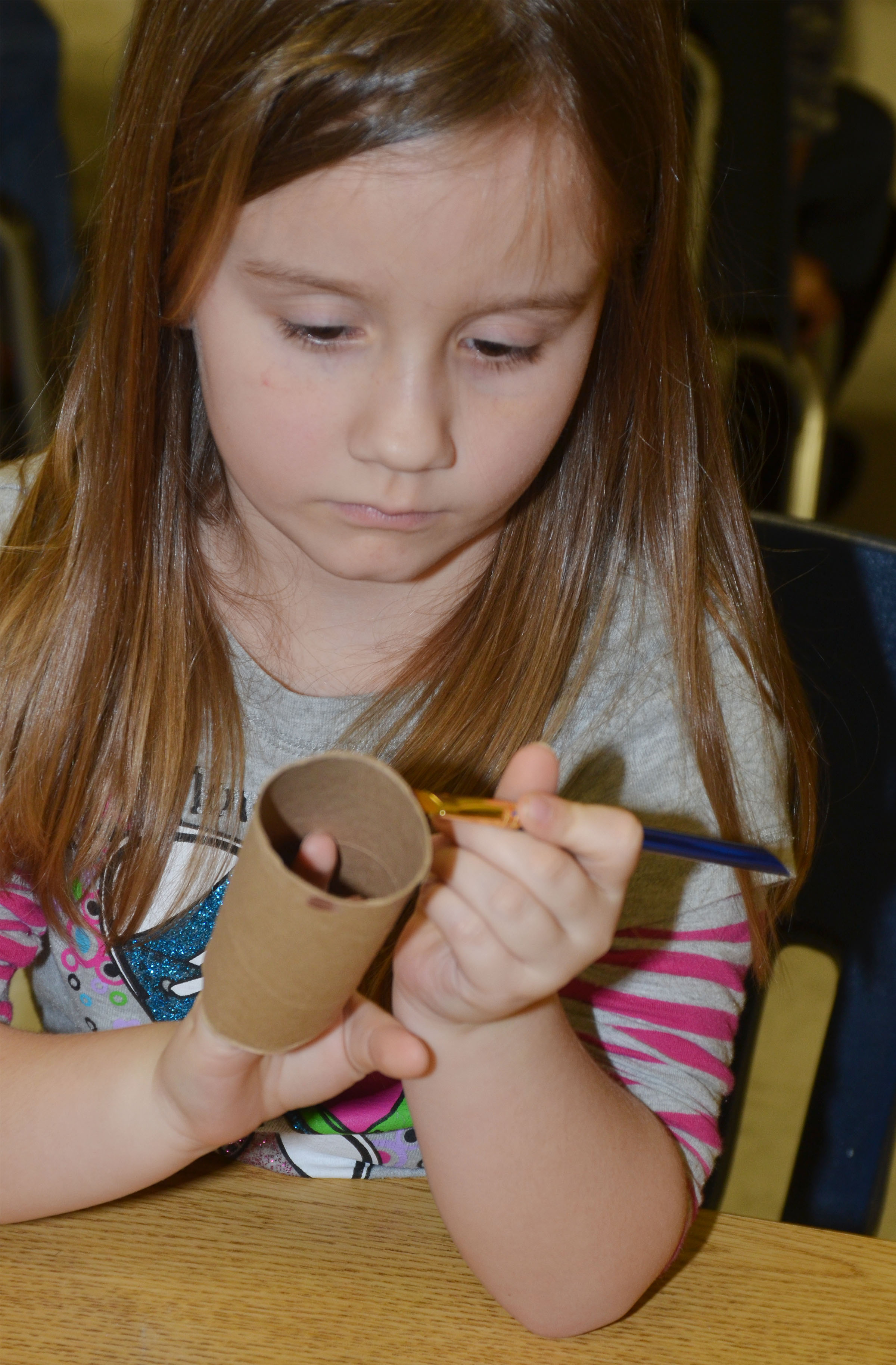CES kindergartener Jewell Brewster paints her toilet paper roll.
