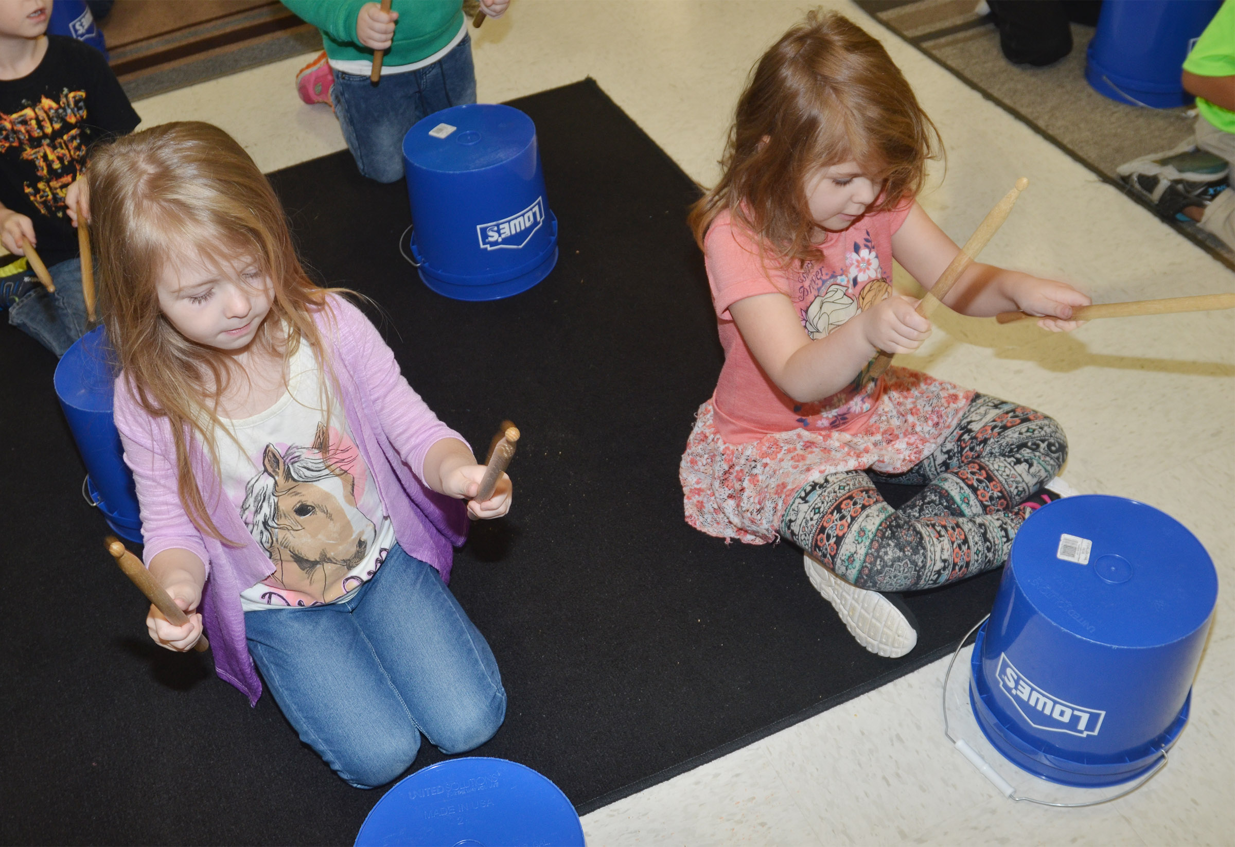 CES kindergarteners Jewell Brewster, at left, and Aubrey Wilson drum.