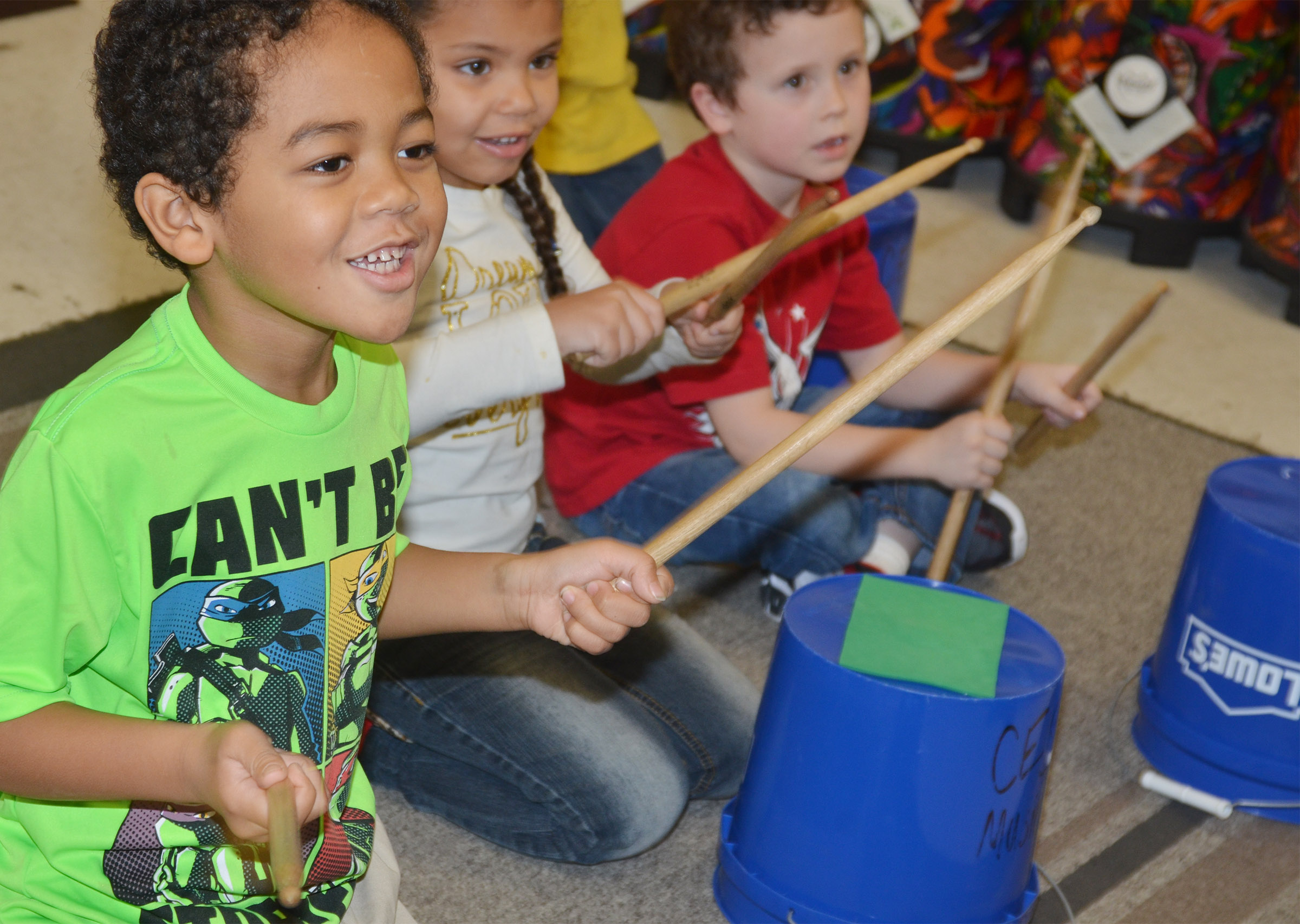 CES kindergartener Tyler Branch smiles as he plays the drums.