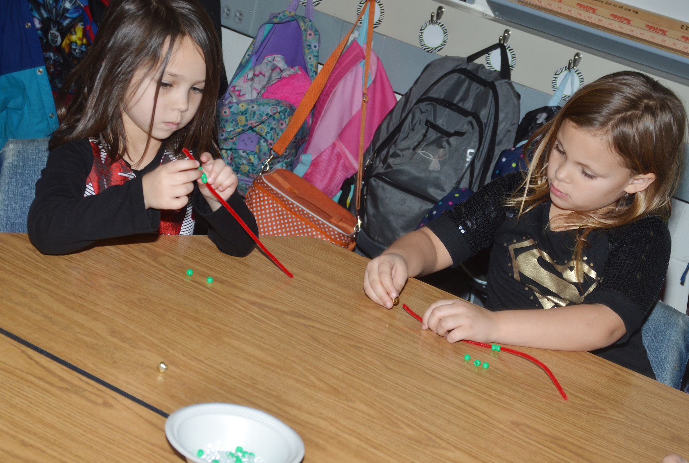 CES kindergarteners Tylee Britton, at left, and Alaziah Smith make jingle bell bracelets.
