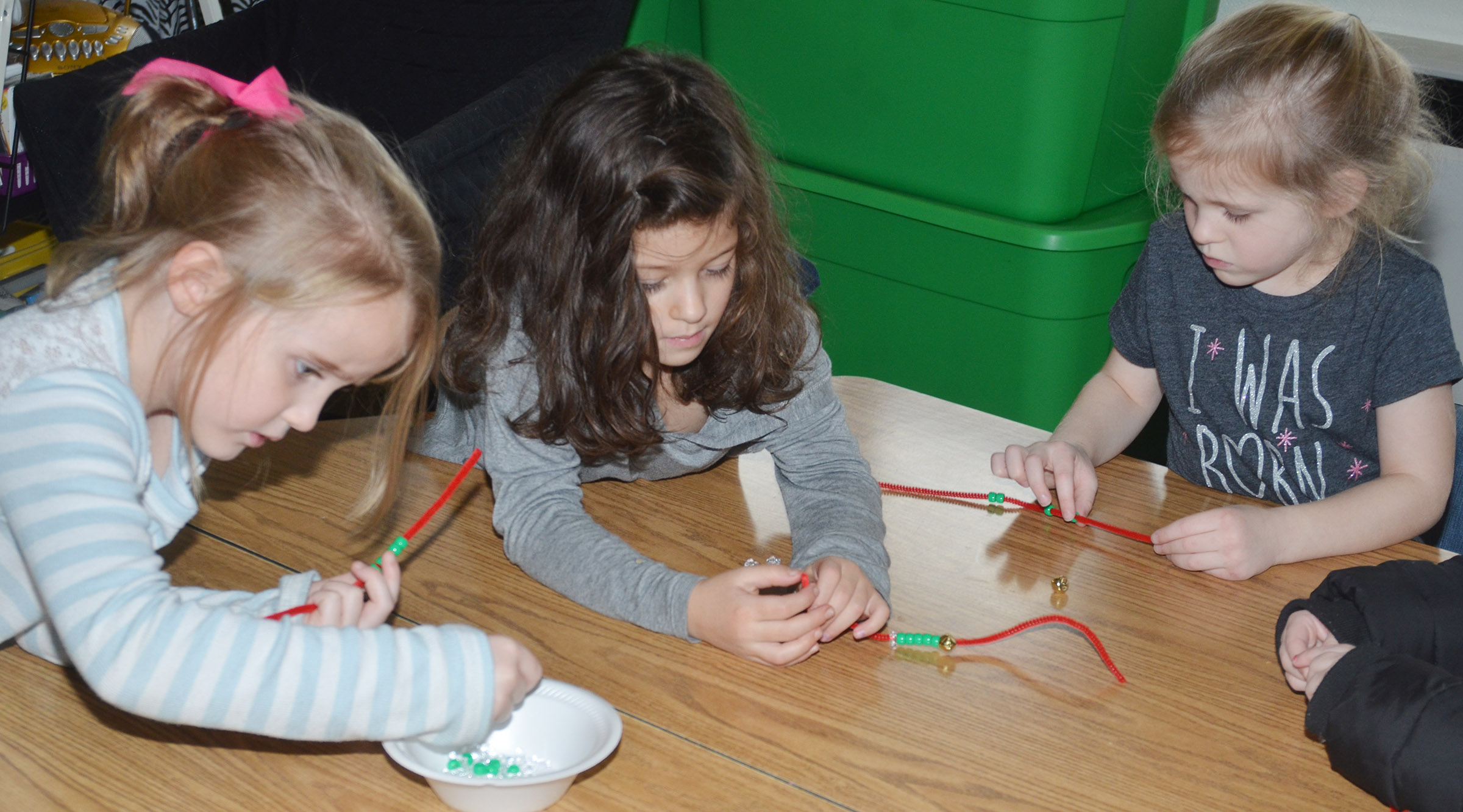 From left, CES kindergarteners Trinity Dye, Norah Adkins and Riley Bright make jingle bell bracelets.
