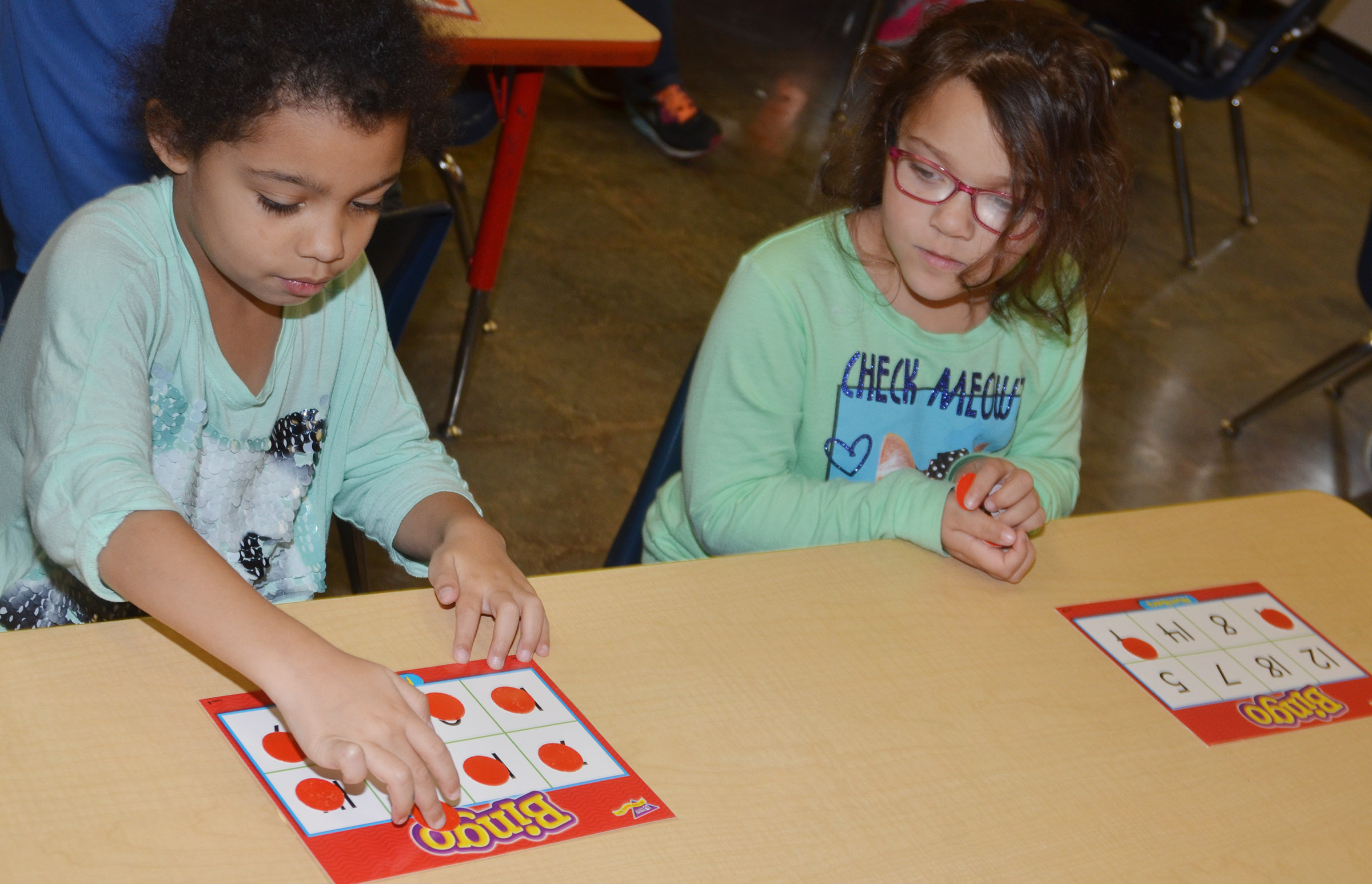 CES kindergarteners Rylee Karr, at left, and Addisyn Taylor play bingo.