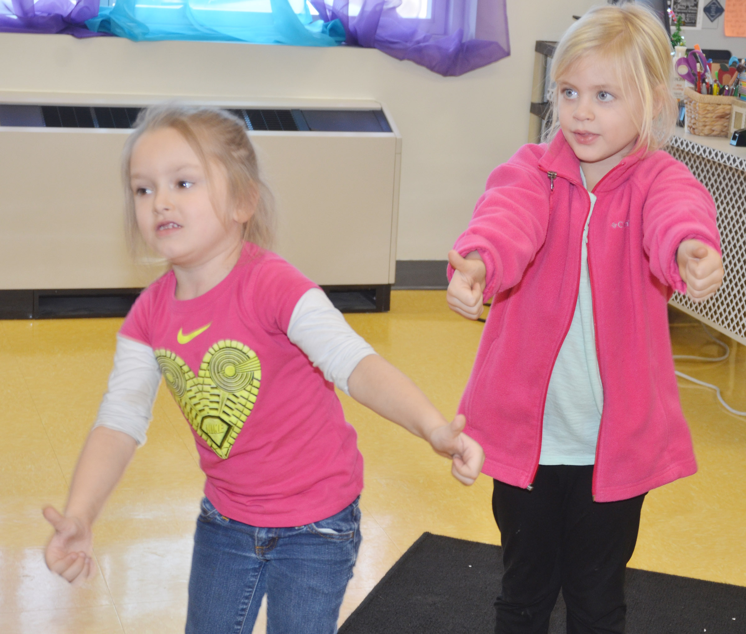 CES kindergarteners Myah Learmond, at left, and Remi Petett dance to a Christmas song.