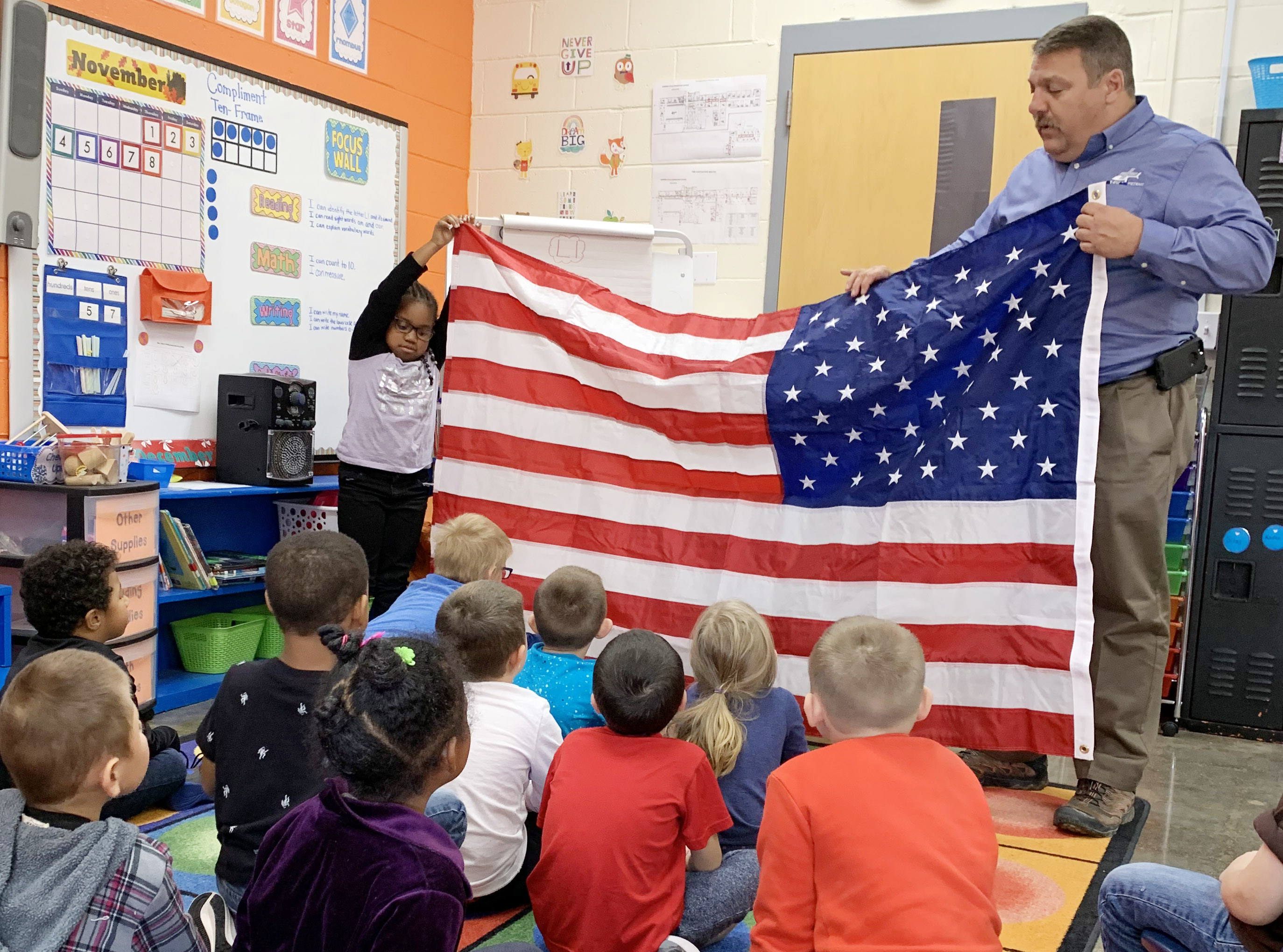 Dan Durham, program director at Air Evac Lifeteam and pastor at Stewarts Creek Baptist Church, speaks to CES kindergarteners about the American flag. At left, kindergartener Kyona Mitchell holds the flag with Durham.