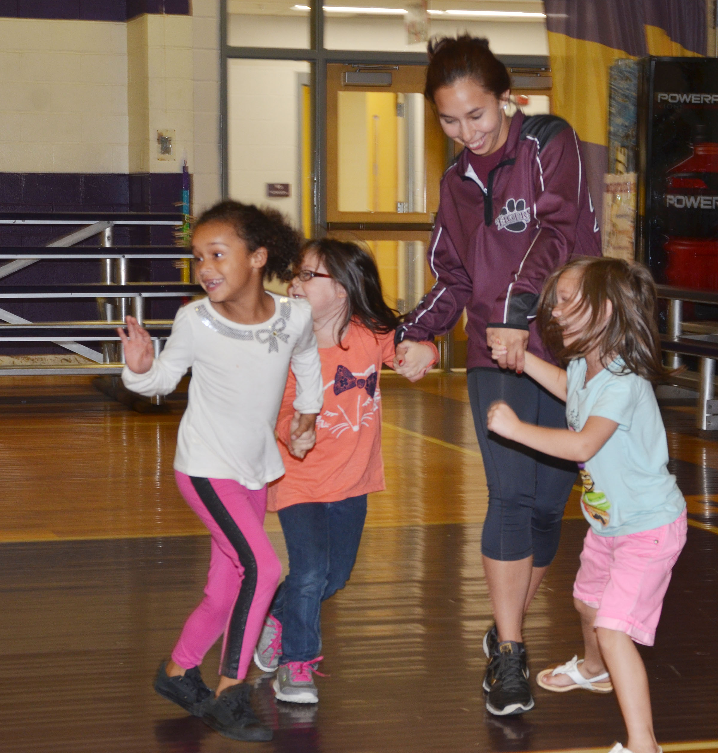 CU wrestler and education student Maria Ramos plays freeze tag with CES kindergarteners. From left are Jyra Welch, Trinity Clark and Addison Perkins.