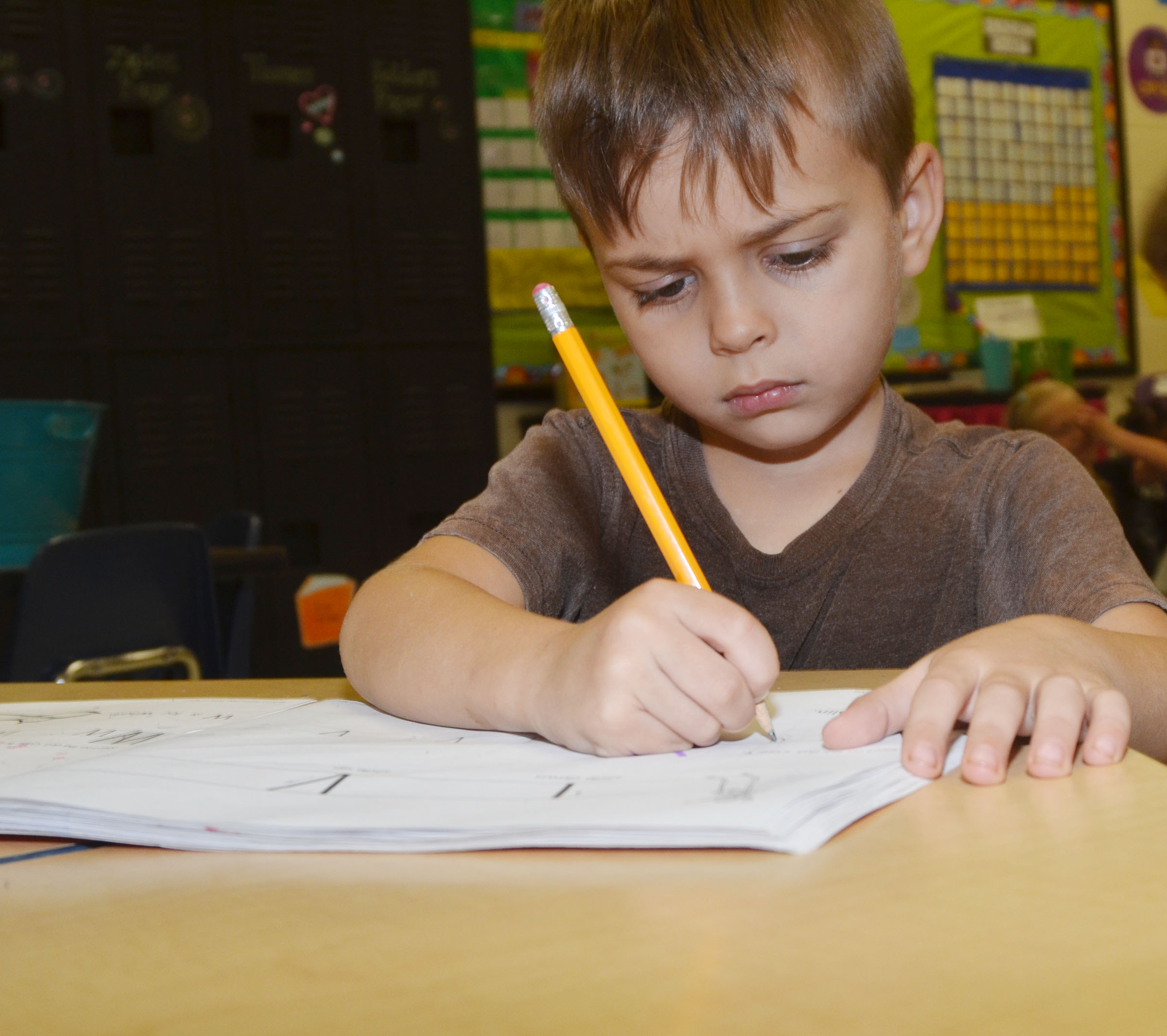 CES kindergartener Michael Terry concentrates as he writes the letter V.