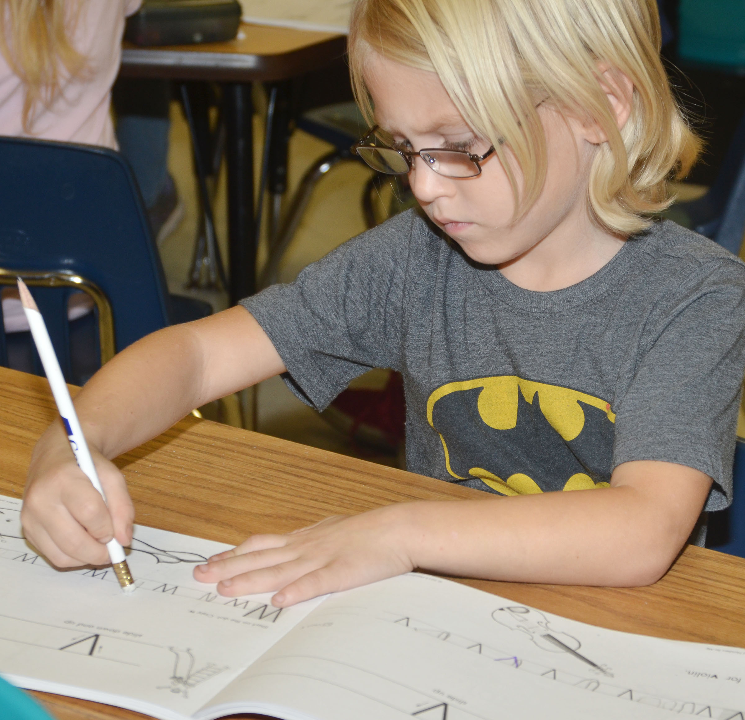 CES kindergartener Linken White concentrates as he writes the letter V.
