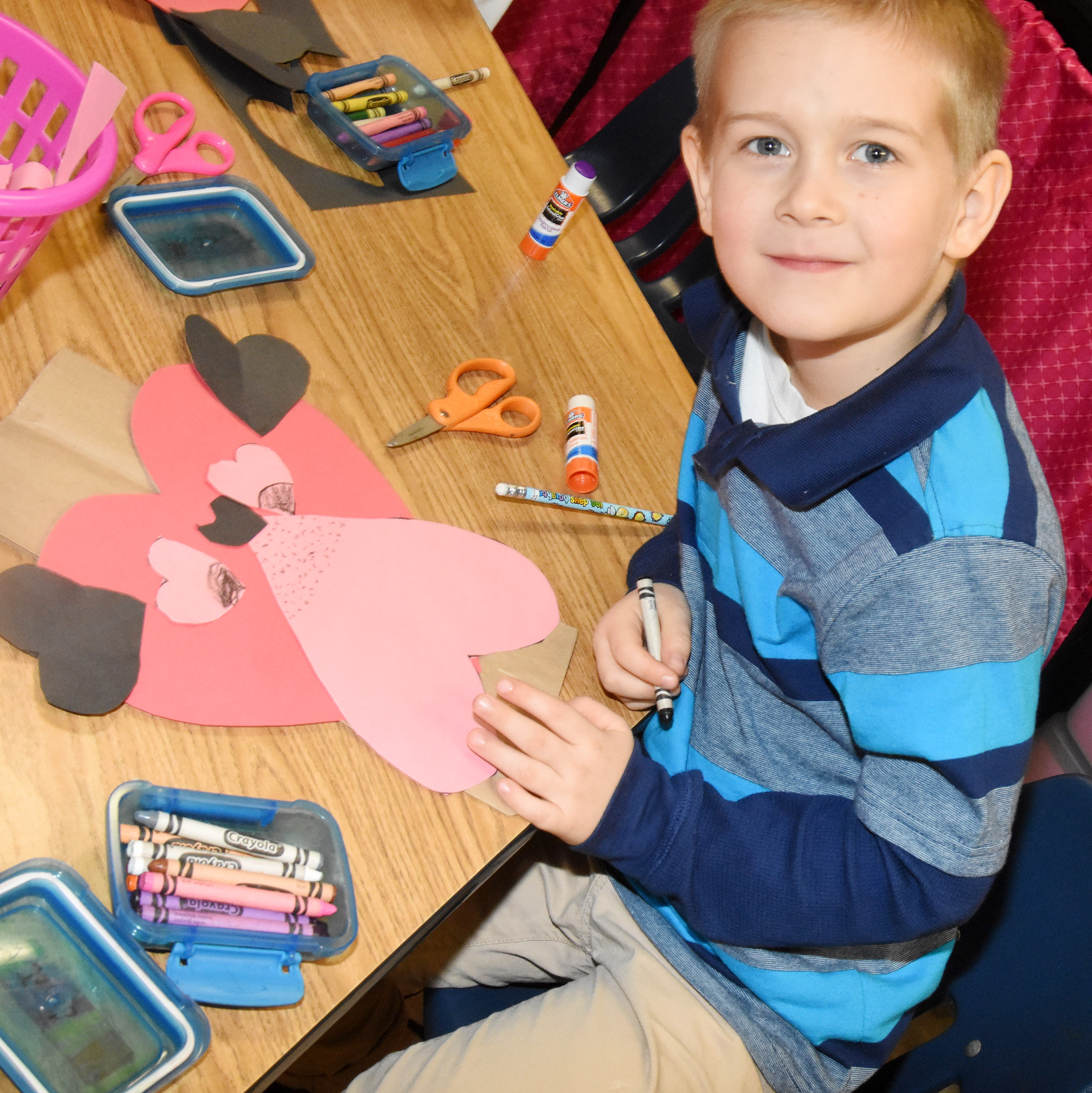 CES kindergartner Jacob Parrish finishes his puppy dog Valentine bag.