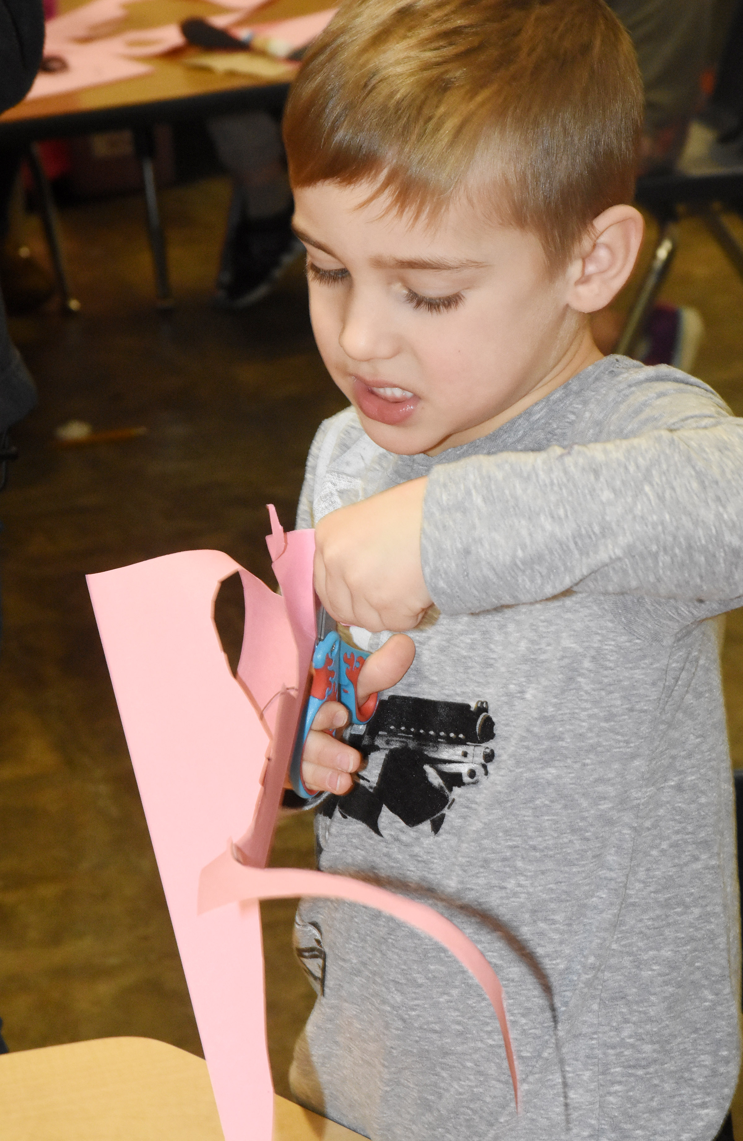 CES kindergartener Dane Gray cuts out hearts to make his puppy dog Valentine bag.