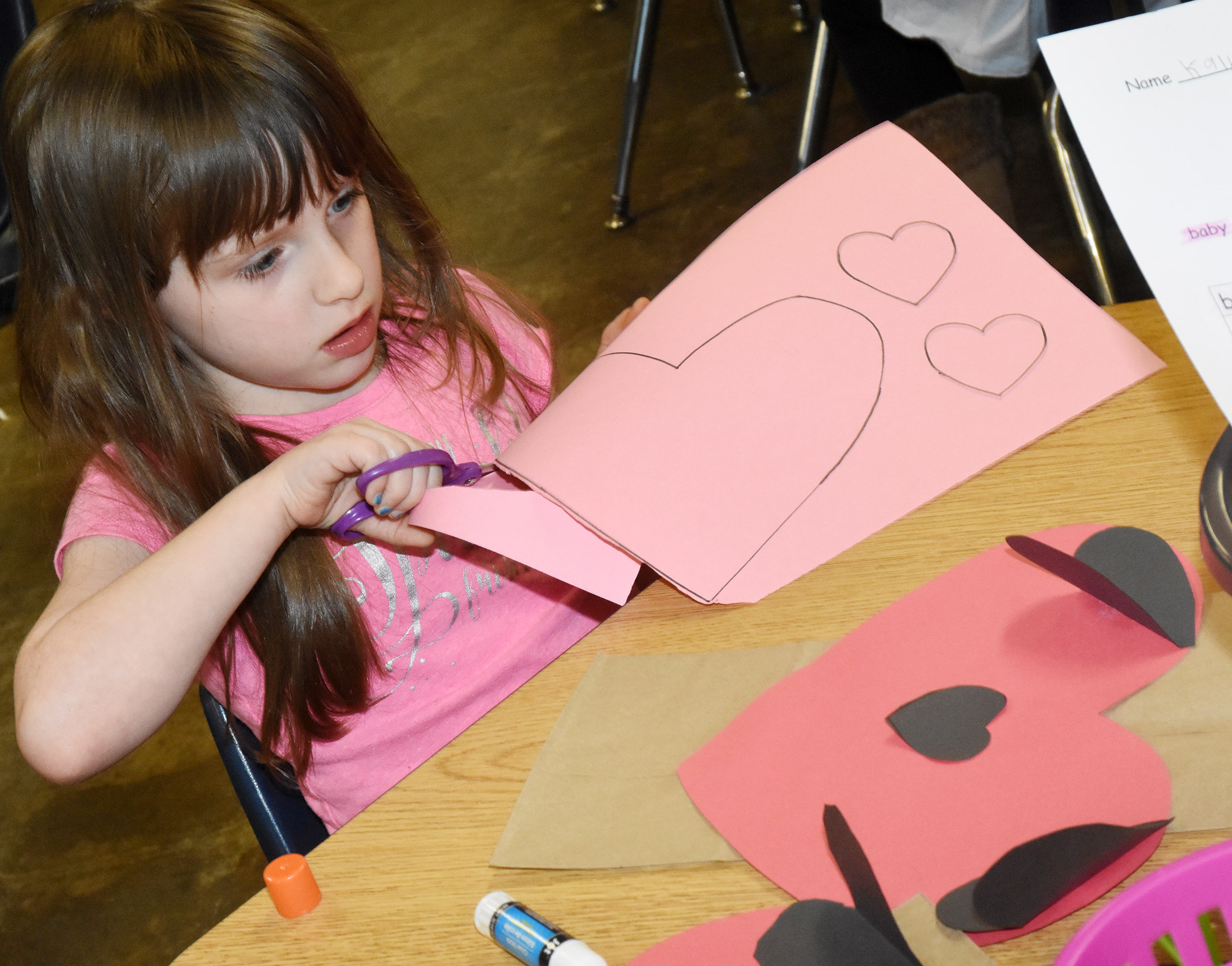 CES kindergartener Kaylee Franklin cuts out hearts to make her puppy dog Valentine bag.