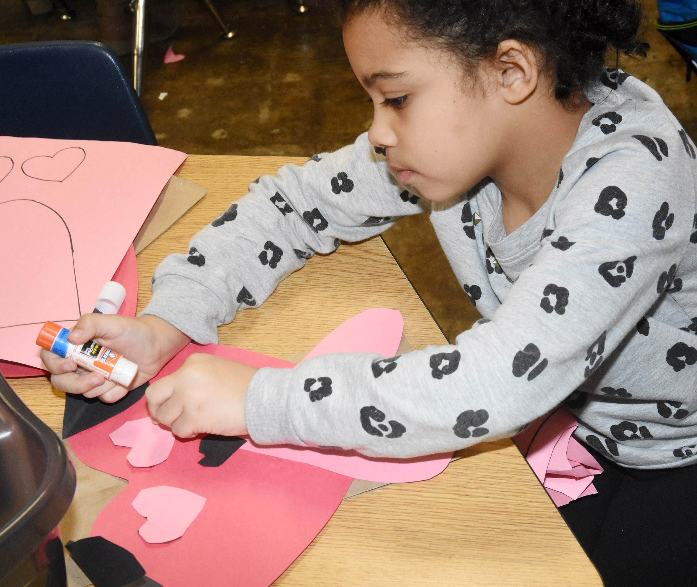 CES kindergartener Rylee Karr glues together her puppy dog Valentine bag.