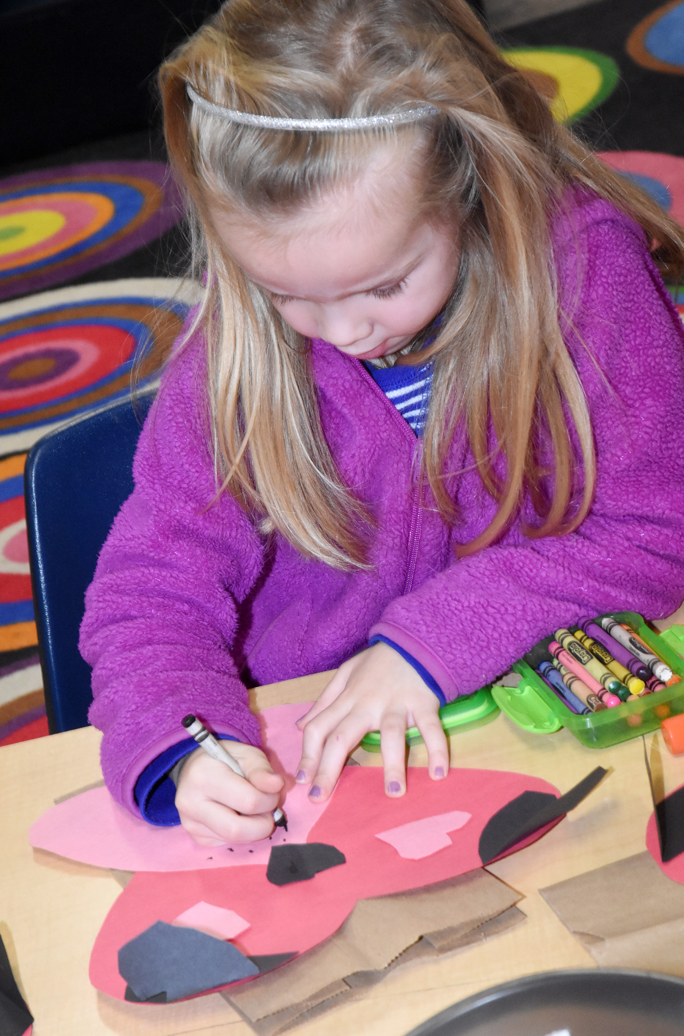 CES kindergartener Trinidy Gribbins draws whiskers on her puppy dog Valentine bag.
