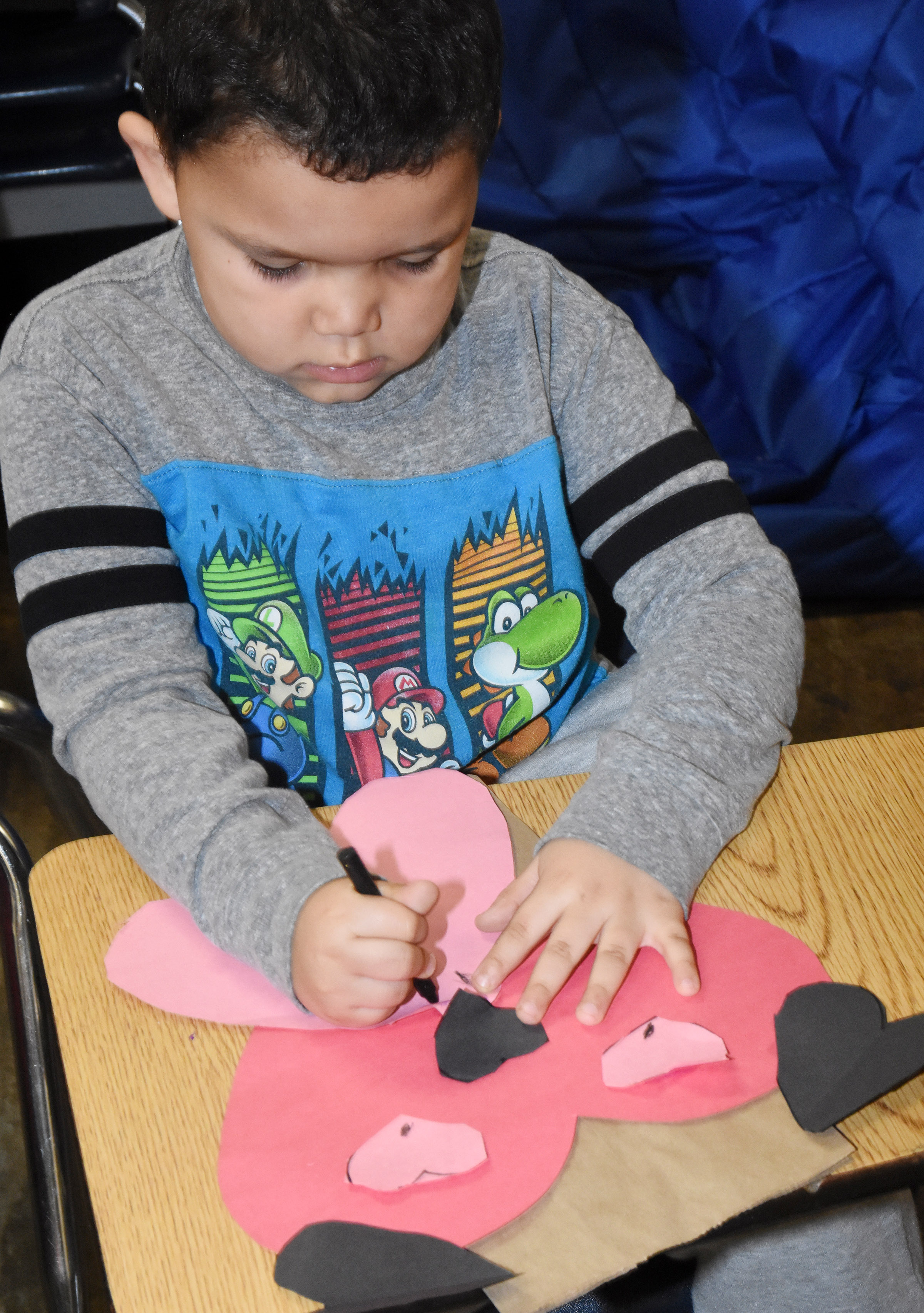 CES kindergartener Kingson Duncan draws whiskers on his puppy dog Valentine bag.