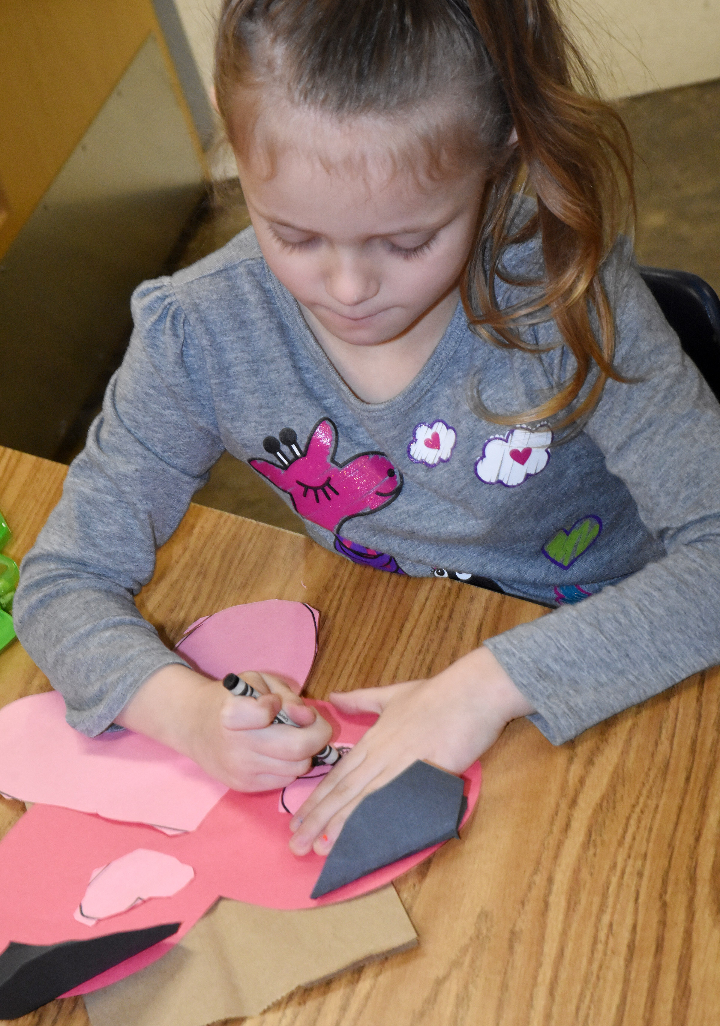 CES kindergartener Aliyah Garrett adds eyes and whiskers to her puppy dog Valentine bag.