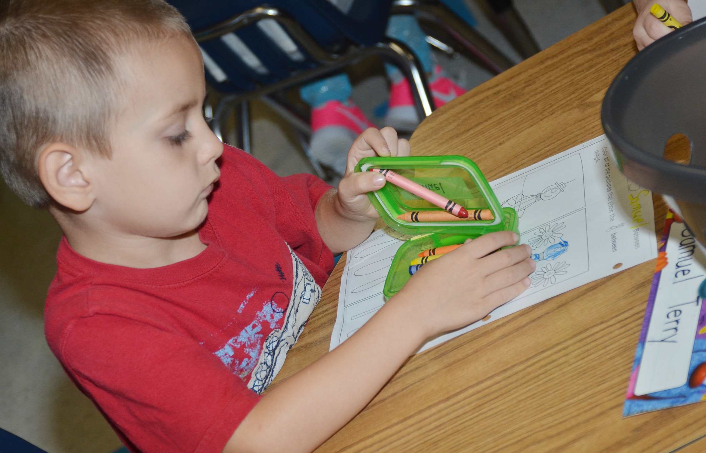 CES kindergartener Samuel Terry looks for a crayon as he colors his worksheet.