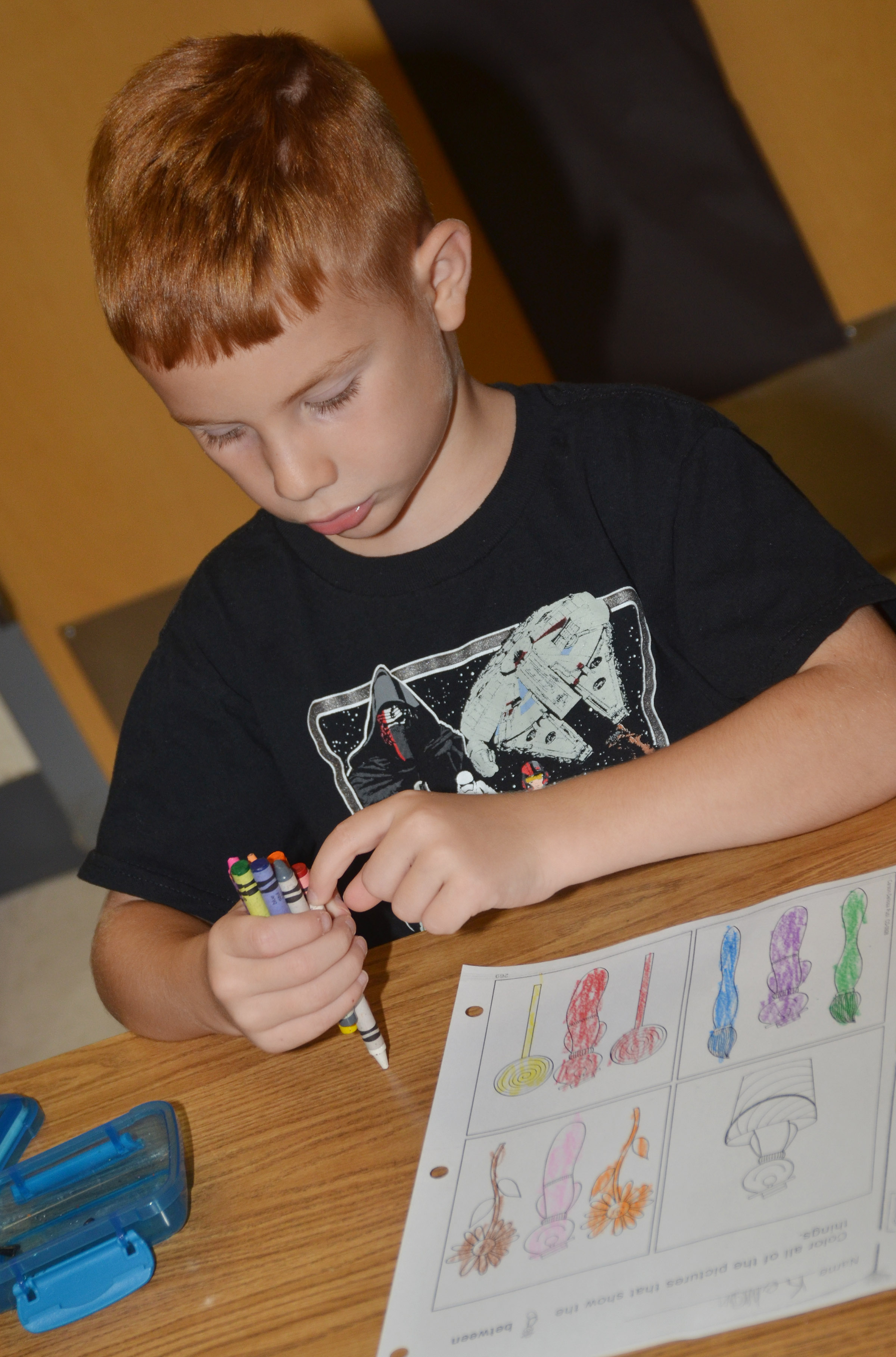CES kindergartener Kennon Dotson organizes his crayons after coloring his worksheet.