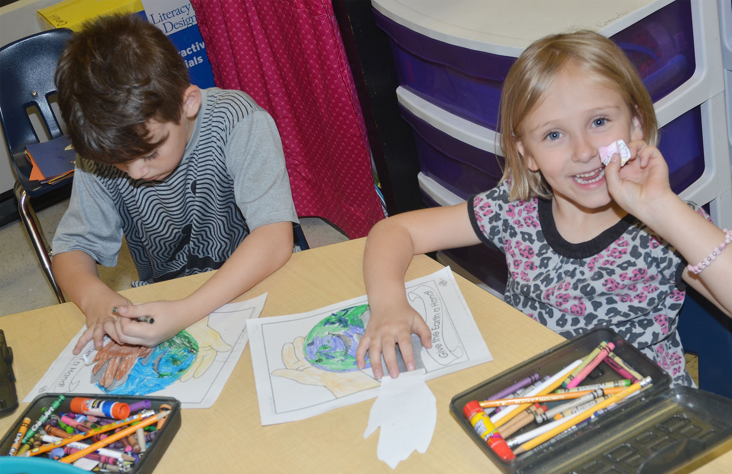 CES kindergarteners Bentley Shively, at left, and LeeAnna Garvin color pictures of the Earth.