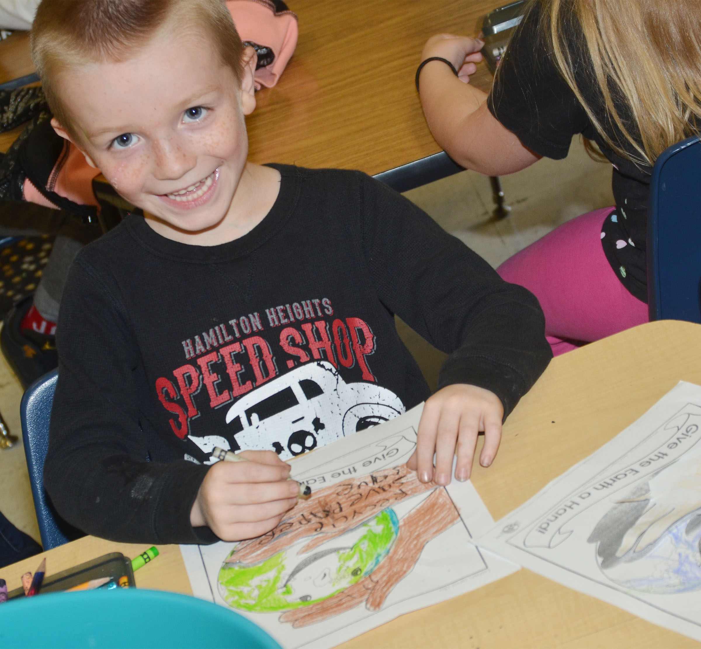 CES kindergartener Jason Eggers colors a picture of the Earth.