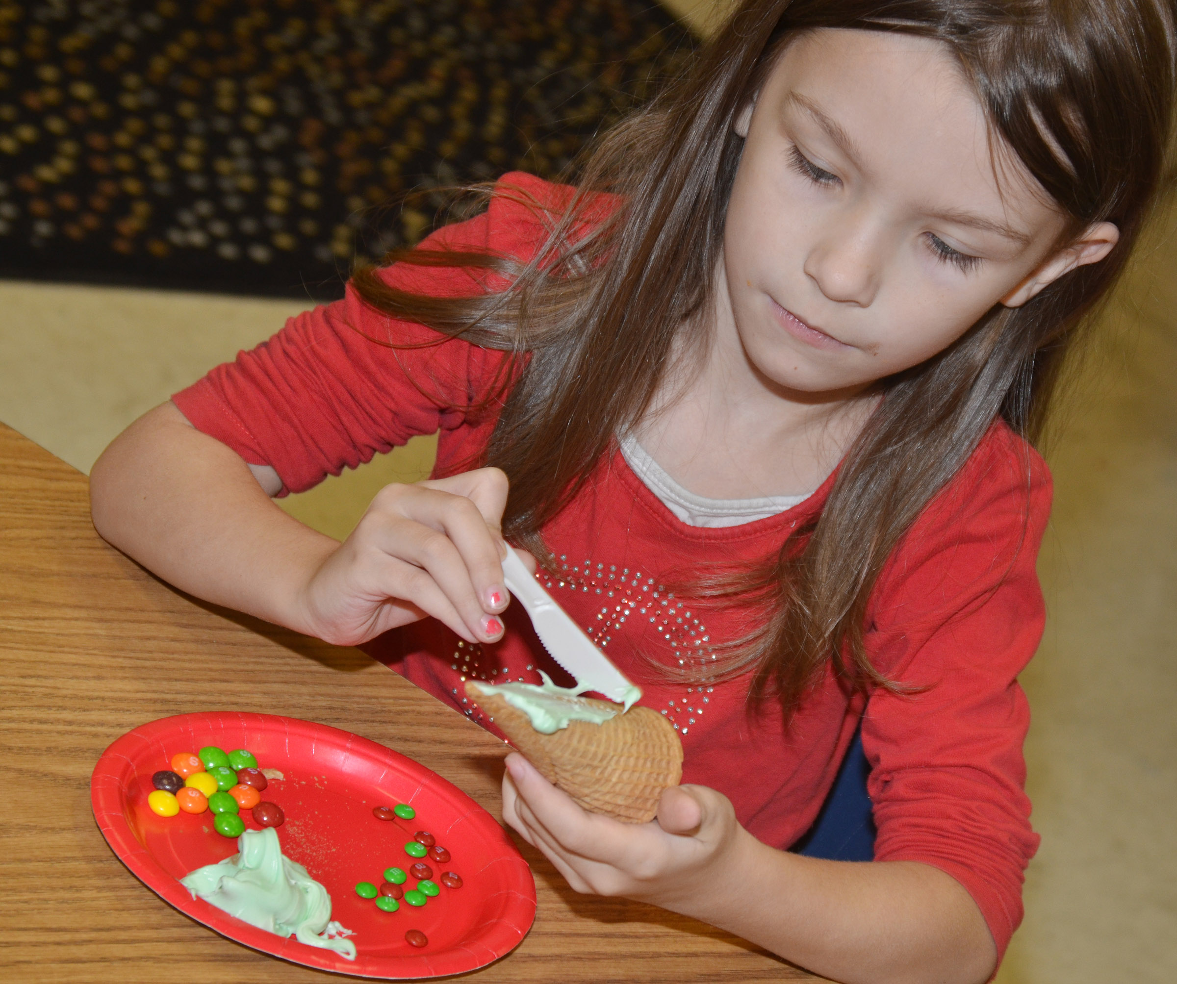 CES kindergartener Melody Ward adds icing to her Christmas tree.
