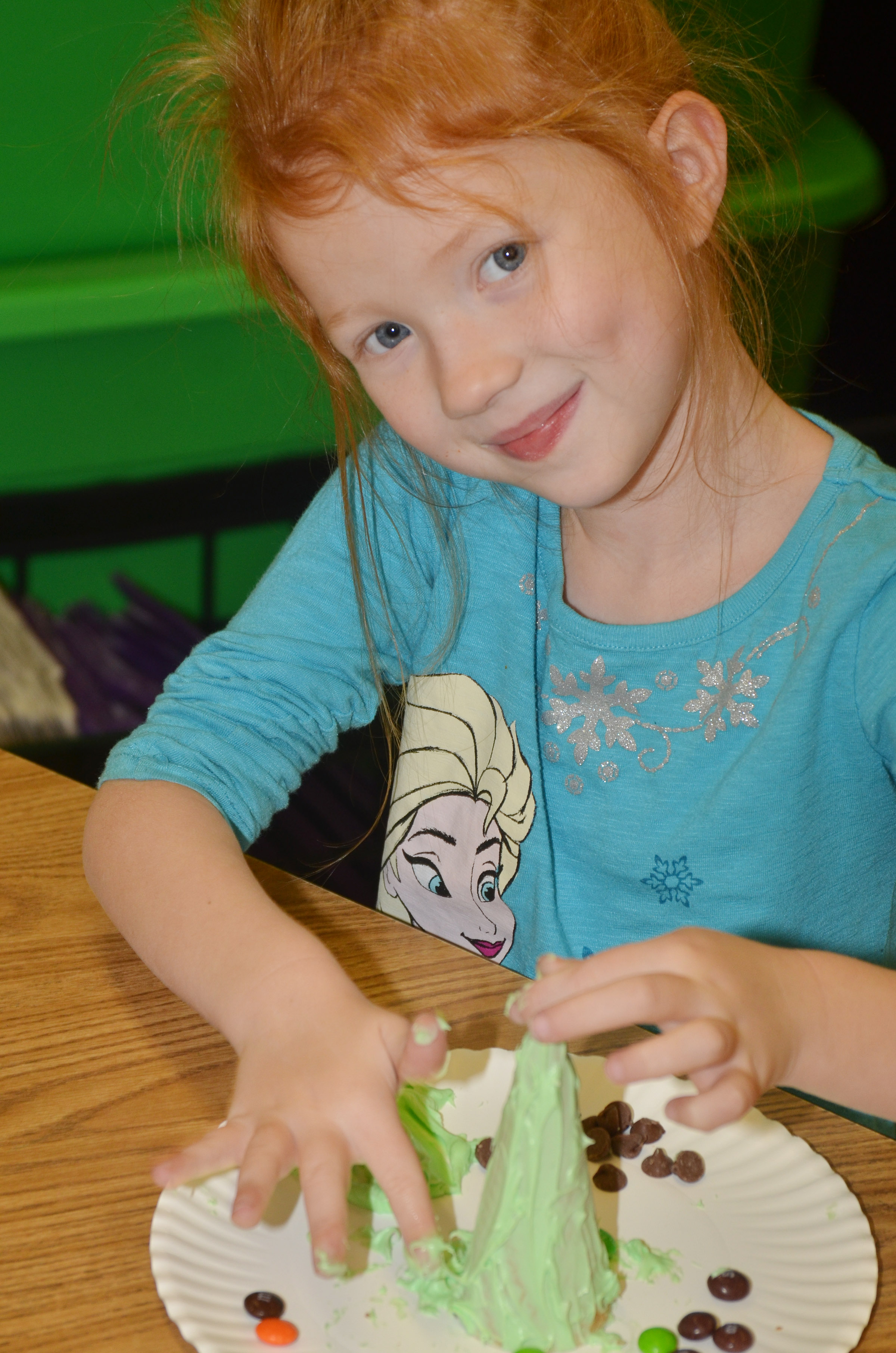 CES kindergartener Isabella Stout adds icing to her Christmas tree.