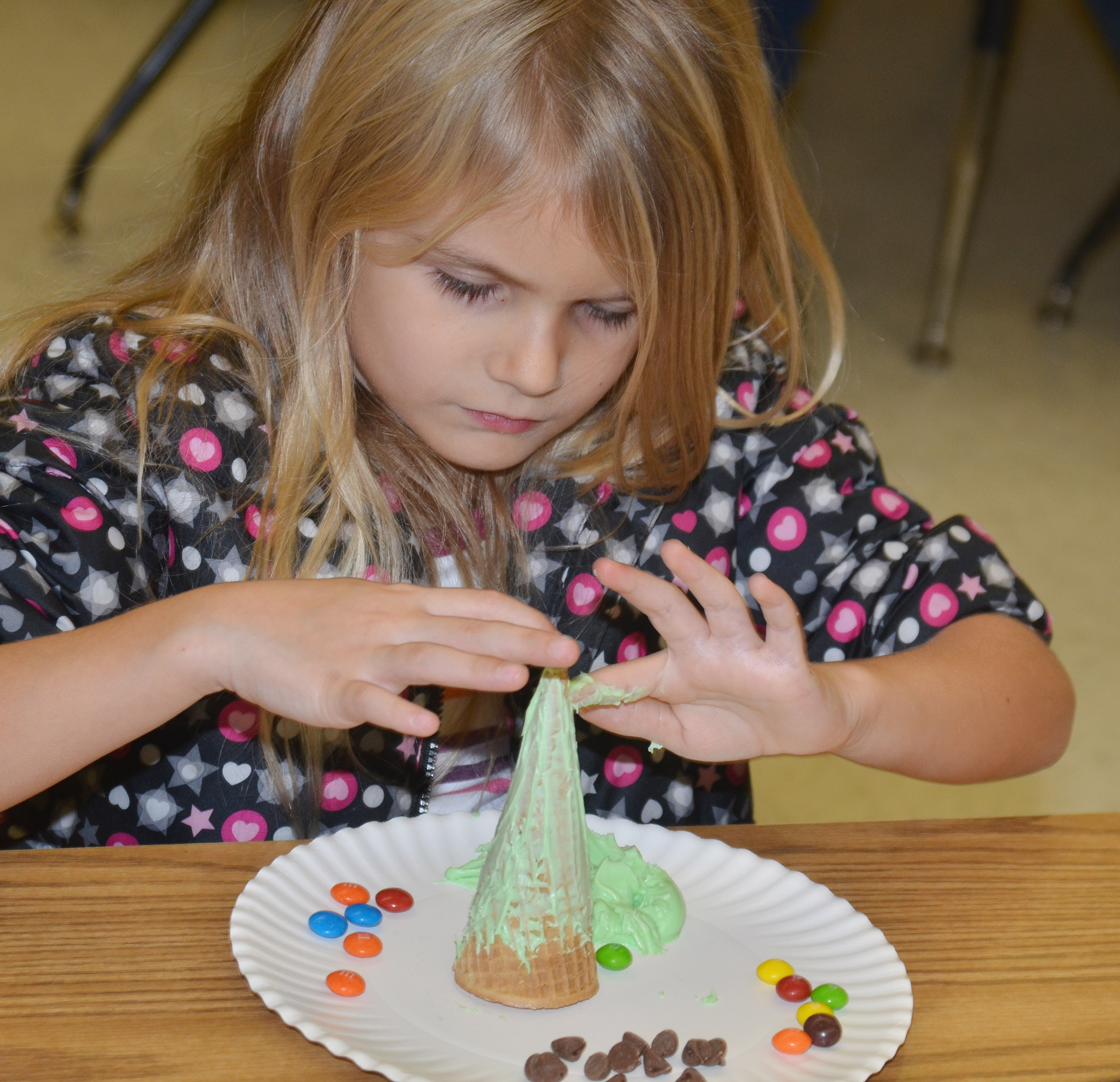 CES kindergartener Gracie Gebler adds icing to her Christmas tree.