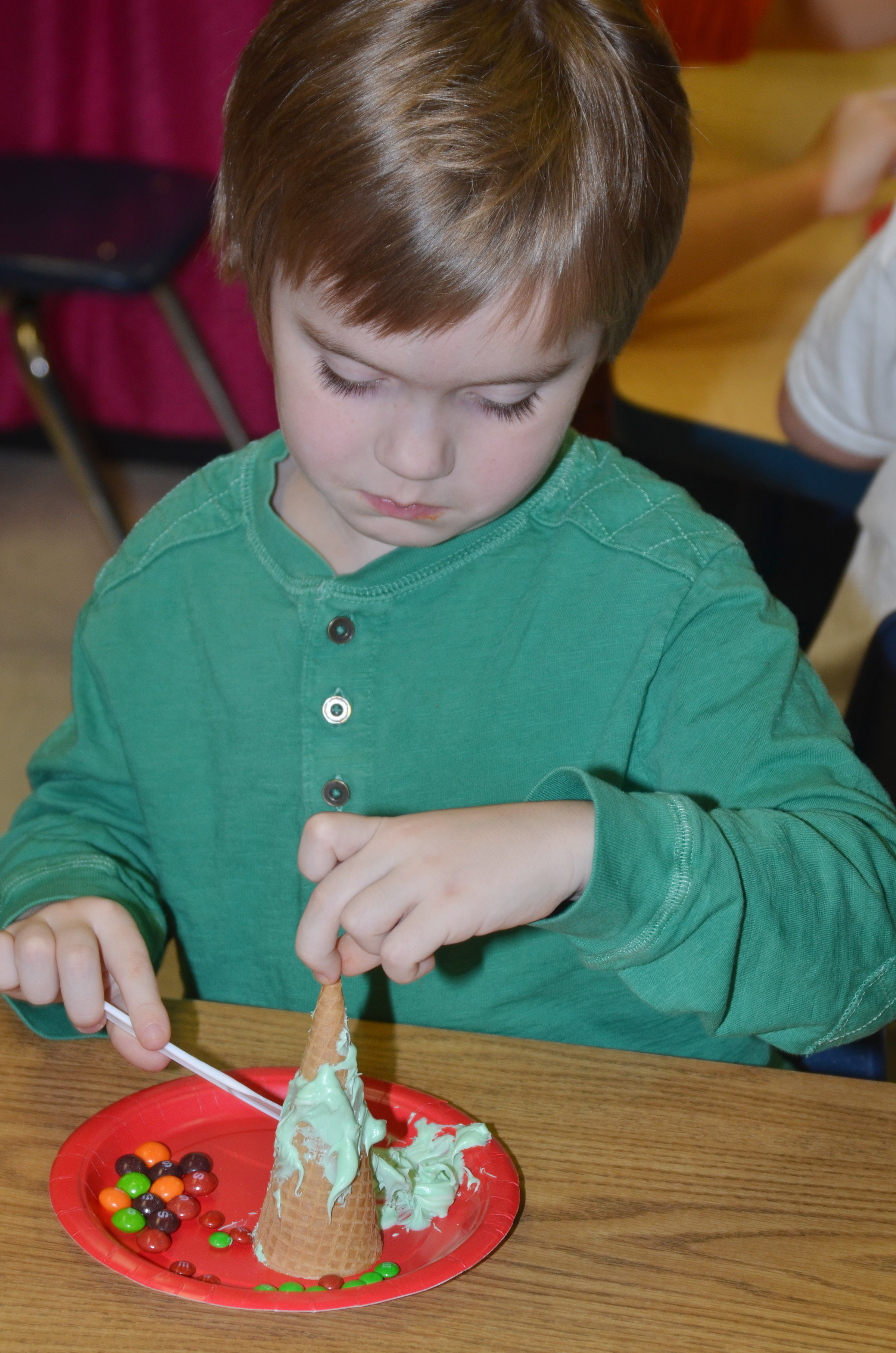 CES kindergartener Gavin Williams adds icing to his Christmas tree.
