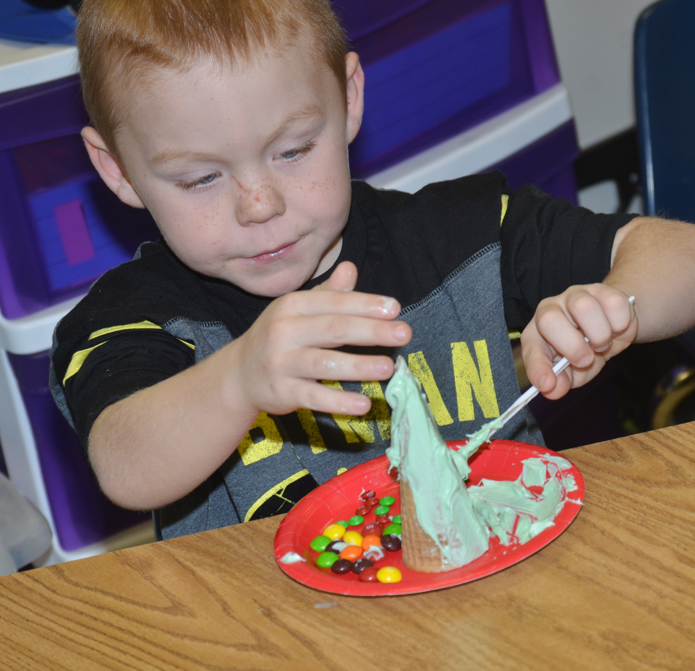CES kindergartener Daven Davis adds icing to his Christmas tree.