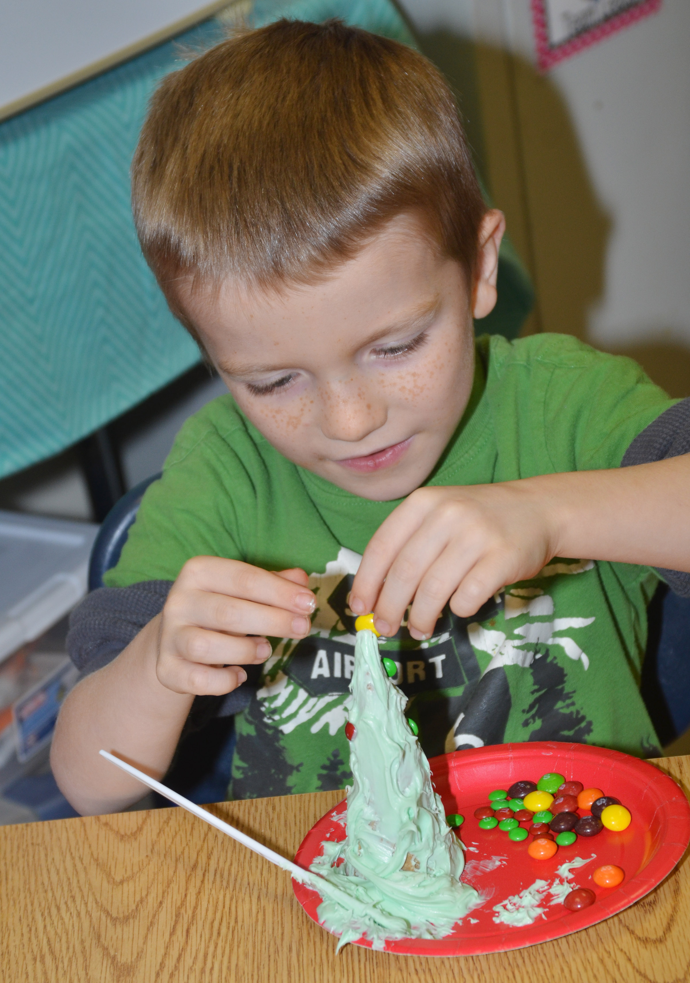CES kindergartener Jason Eggers decorates his Christmas tree with Skittles and M&MS.