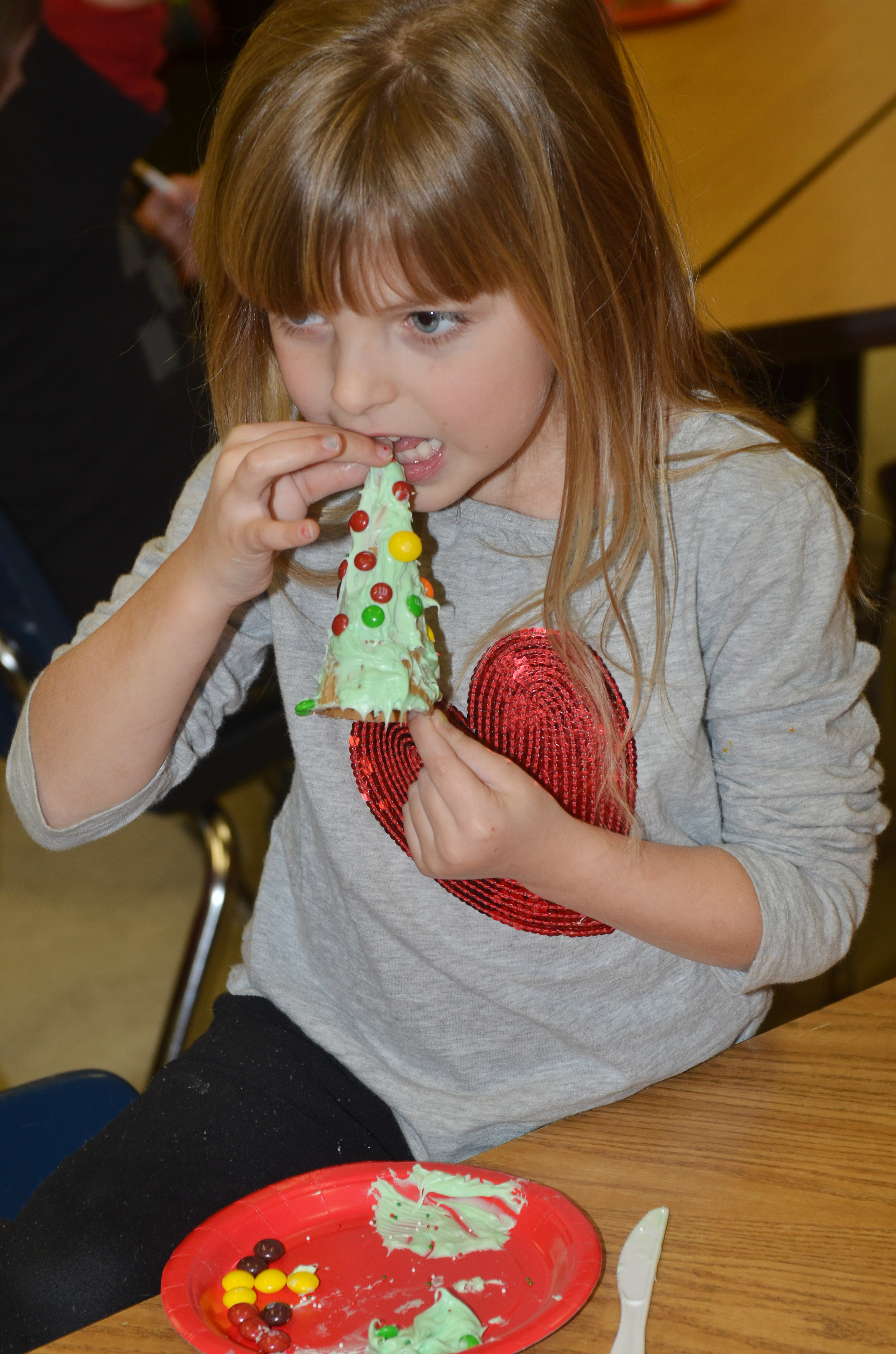 CES kindergartener Madison Wilhoite takes a bite of her Christmas tree.