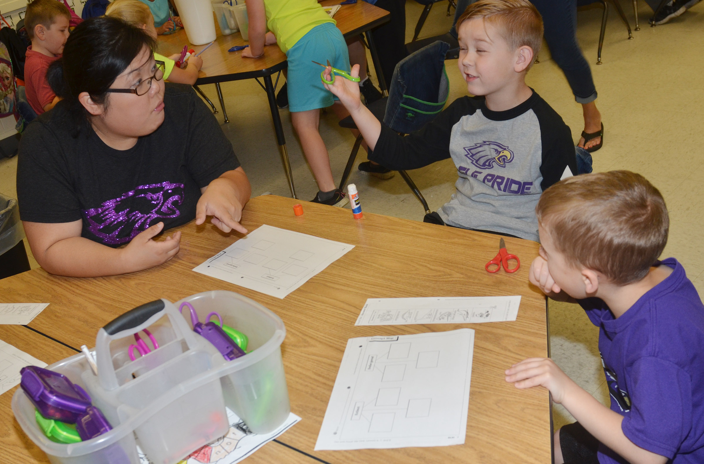 CES kindergarten assistant Brittany Johnson talks to kindergarteners John Hagan Newton, center, and Gavin Paris about extinct and endangered animals.