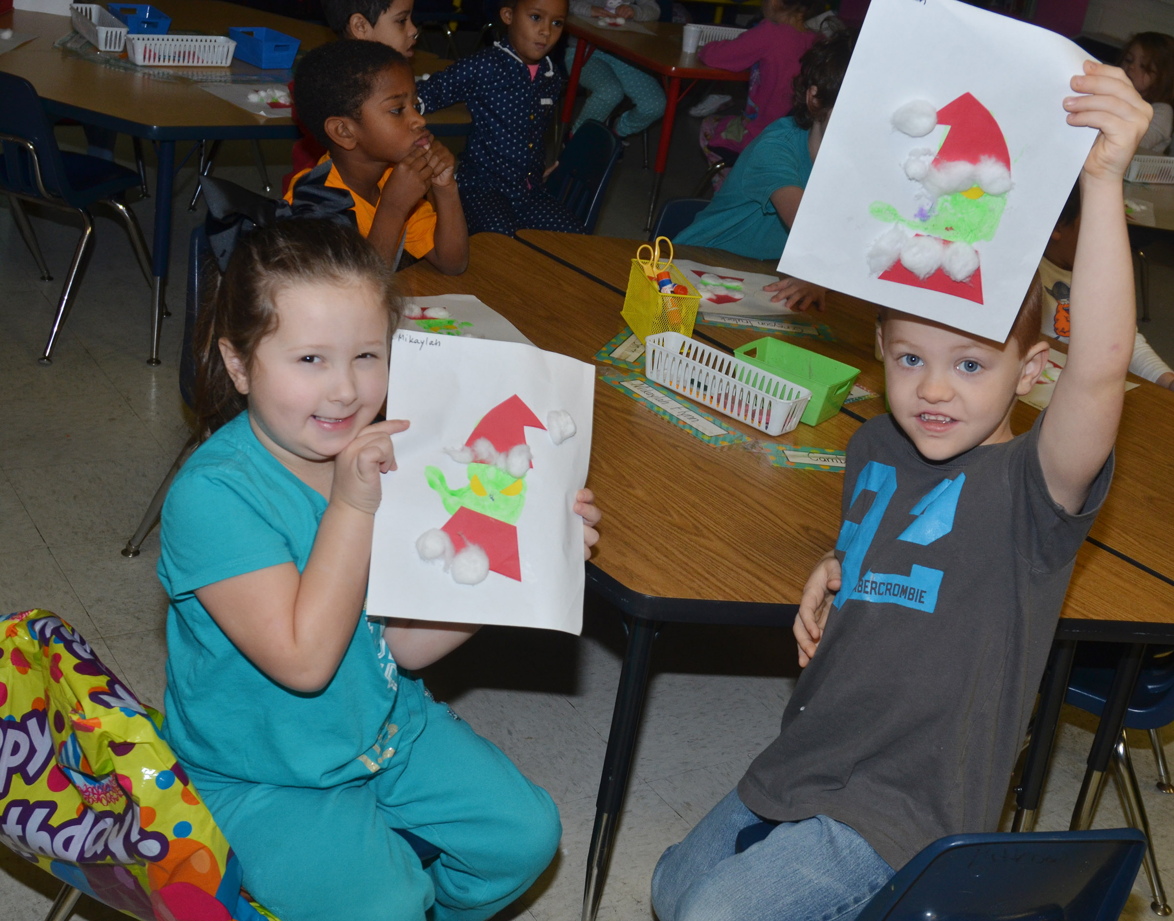 CES kindergarteners Mikaylah Flynn, at left, and Cambrien Couch hold the Grinches they made out of their handprints.
