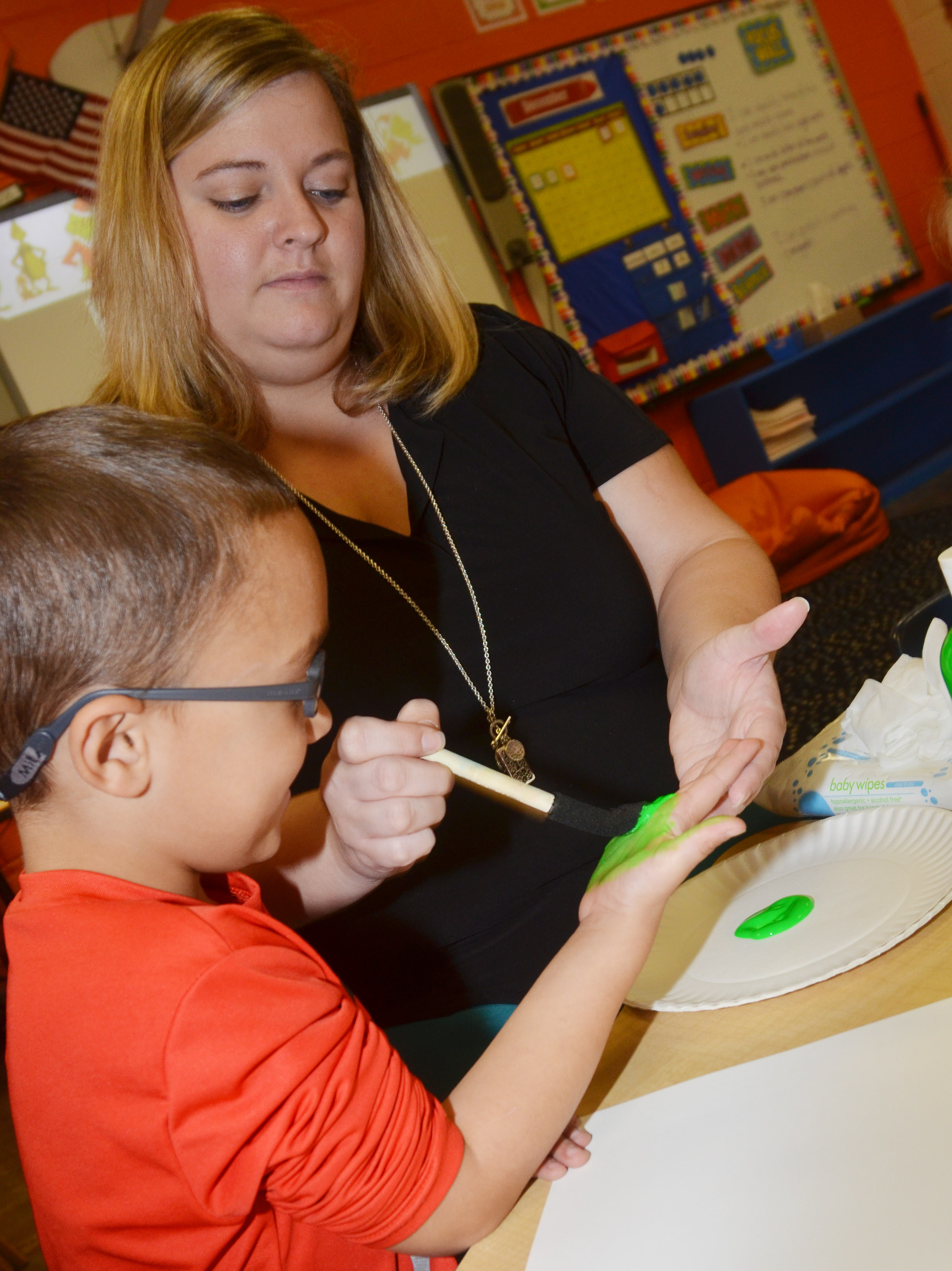 CES kindergarten teacher Kimberly Clark helps Chanler Mann make his Grinch handprint.