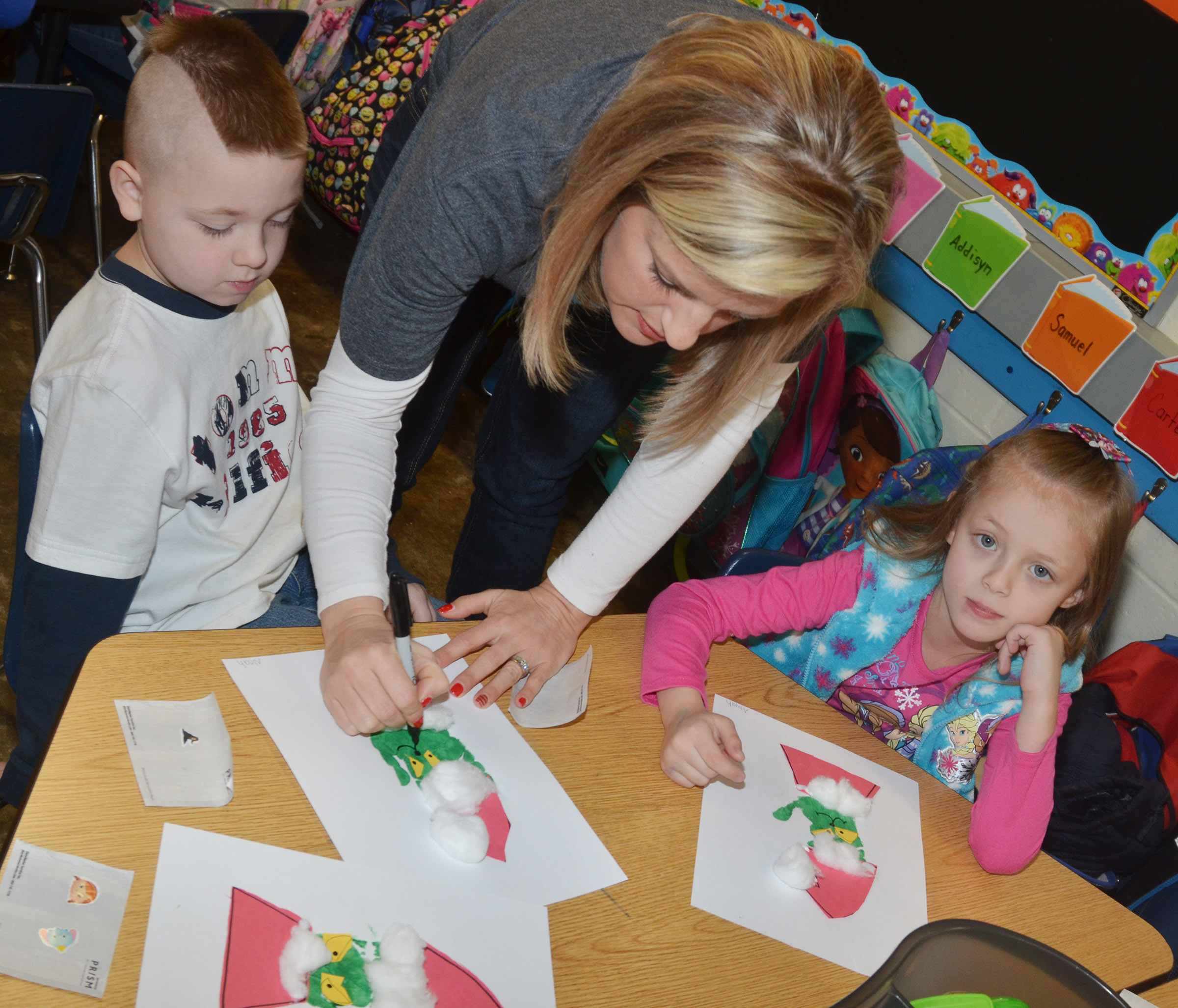 CES kindergarten teacher Leanna Cundiff helps Noah Milburn, at left, and Aliyah Garrett finish their Grinch handprints.
