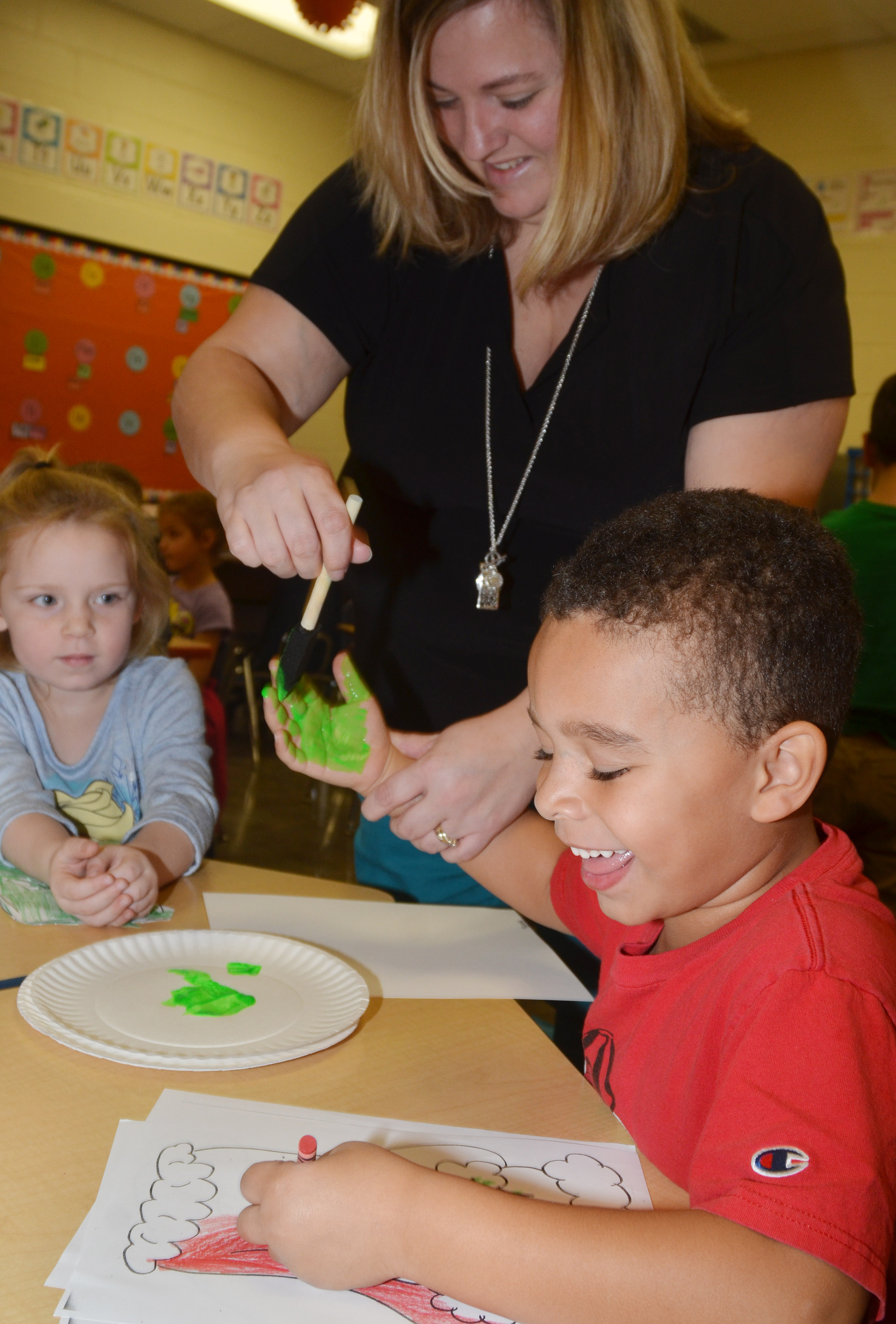 CES kindergarten teacher Kimberly Clark helps Tyrek Moore make his Grinch handprint.
