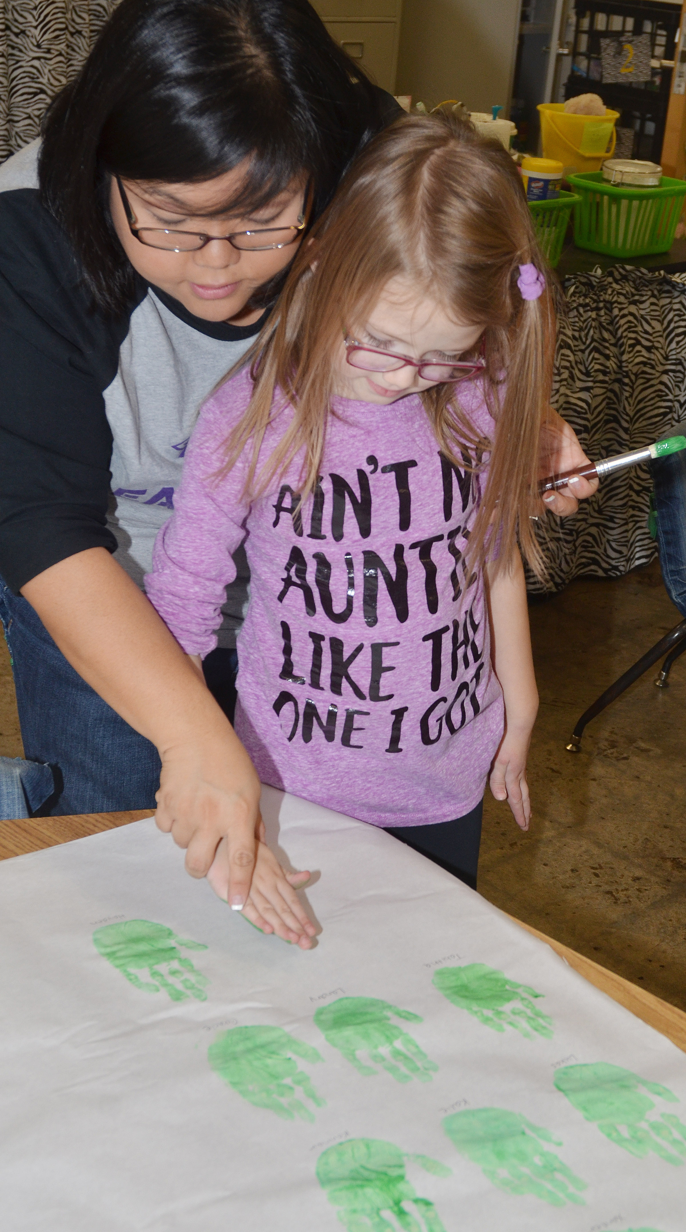 CES kindergarten assistant Brittany Johnson helps Emmaline Vespie paint her Grinch handprint.