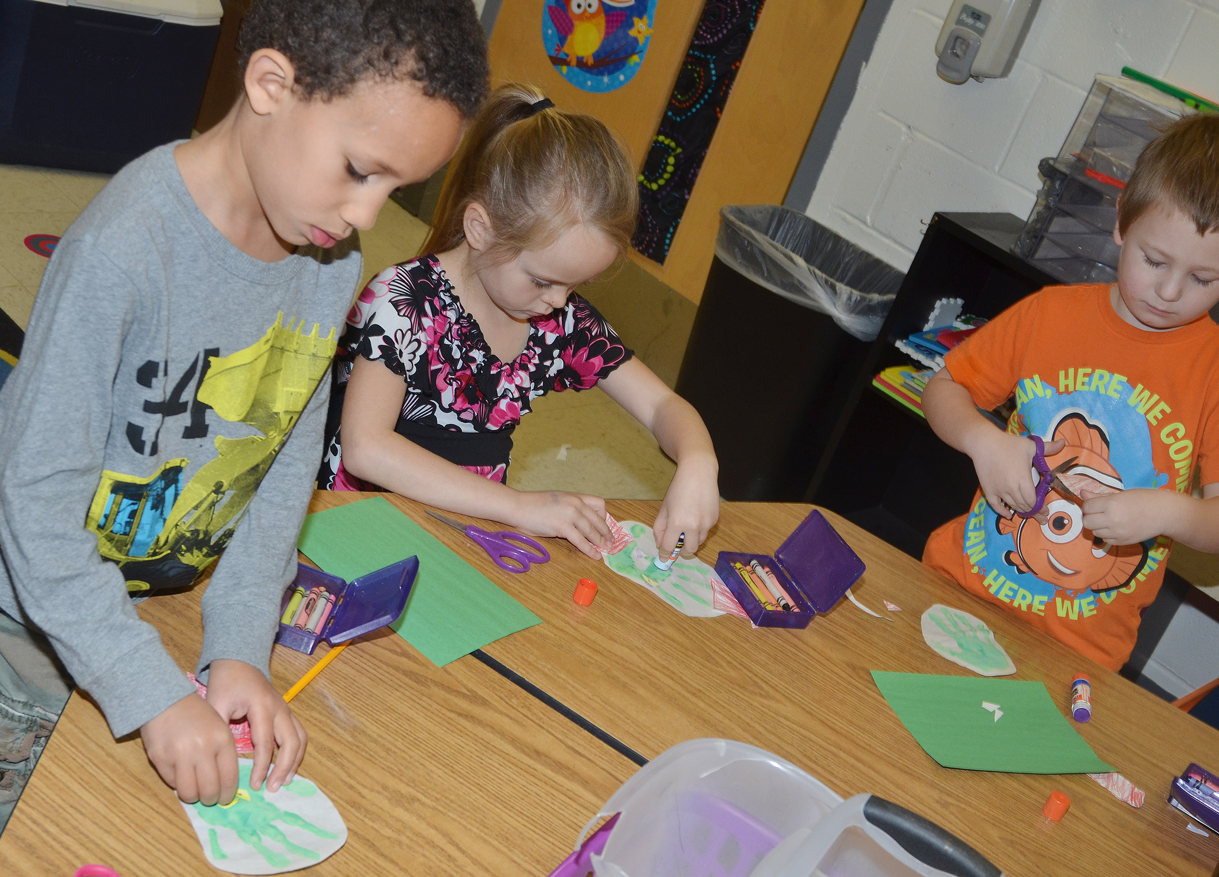 From left, CES kindergarteners Jaxon Williams, Ambie Edwards and Cameron Dean make their Grinch handprints.