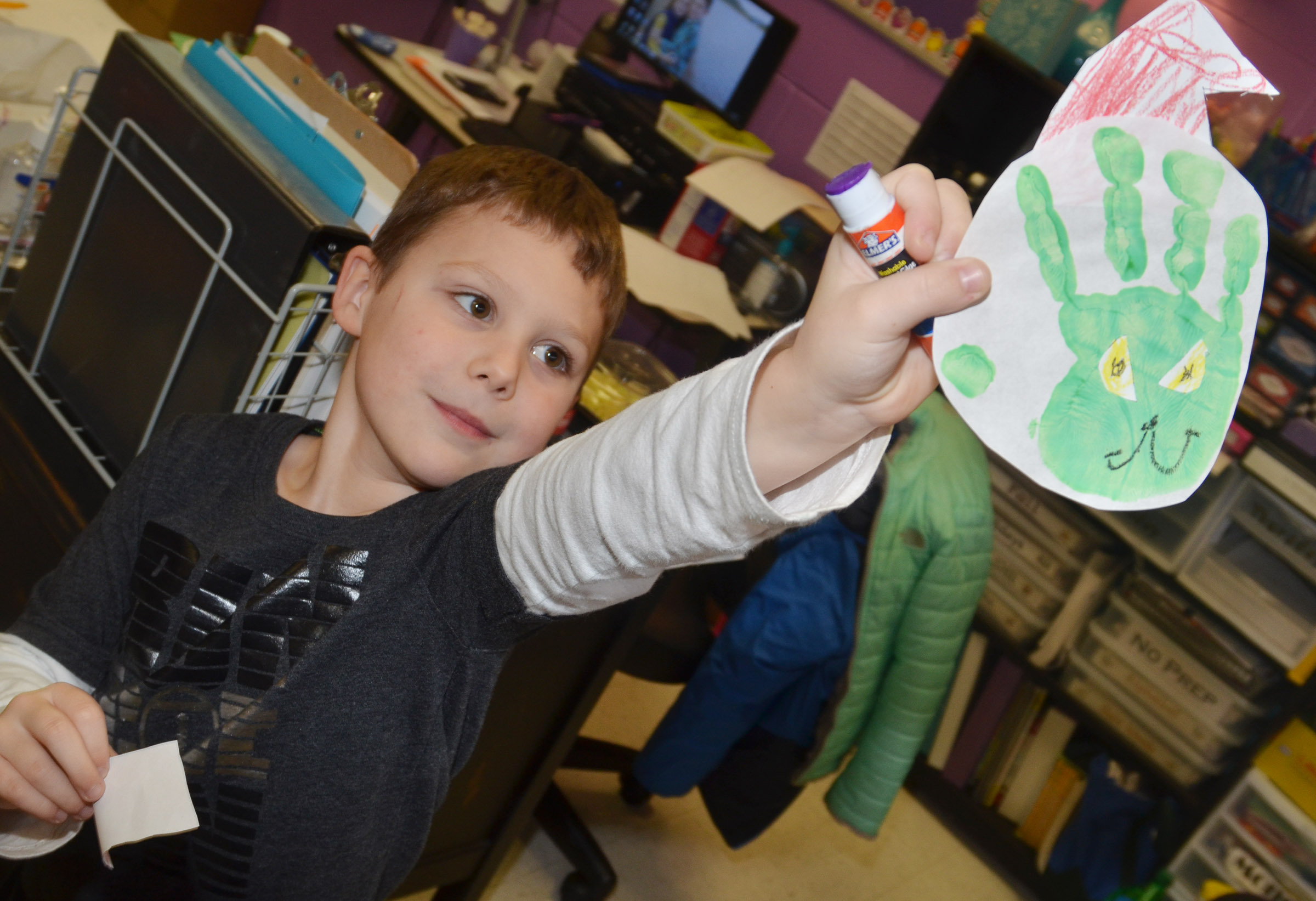 CES kindergartener Kyler Wilson holds his Grinch handprint.