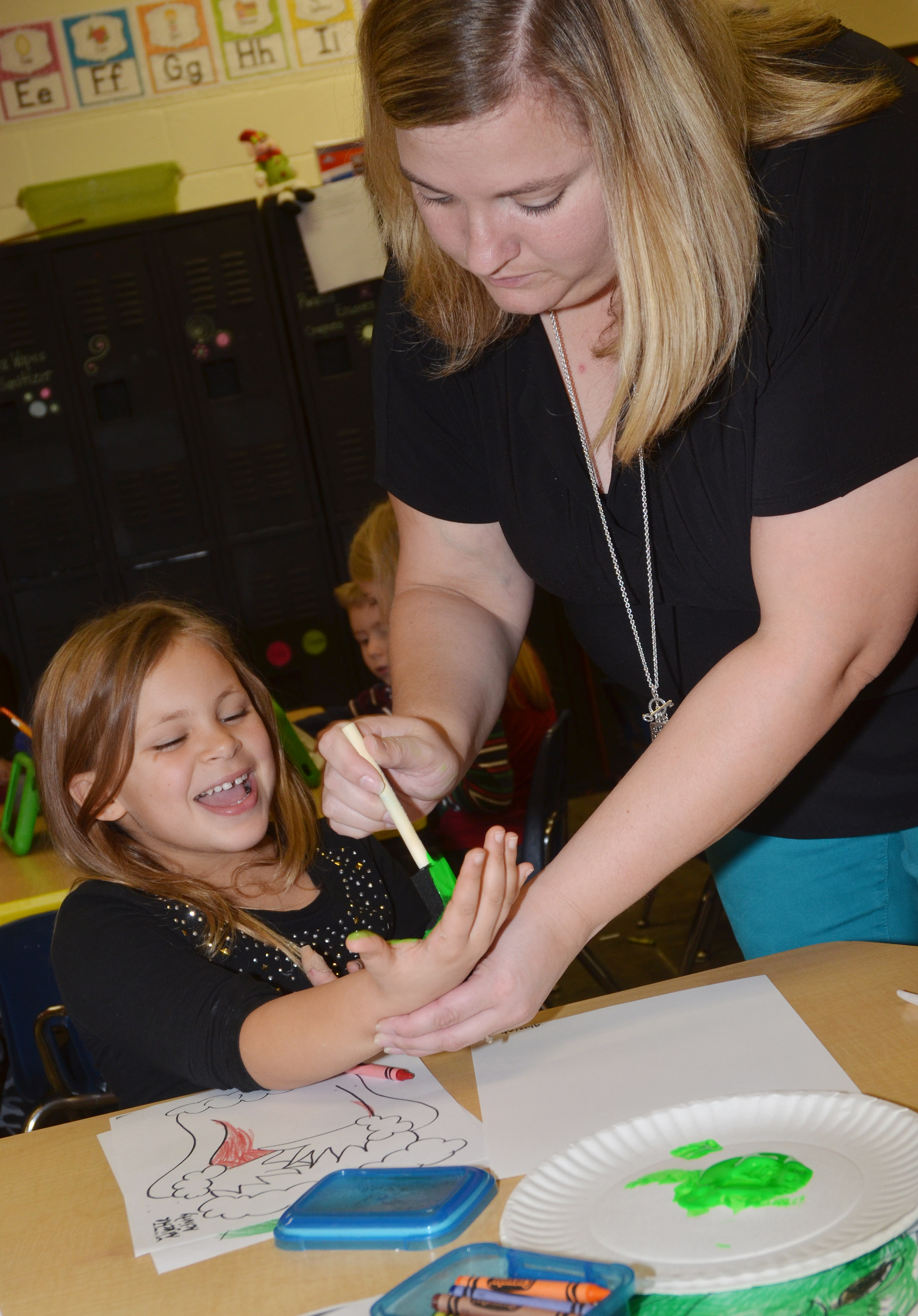 CES kindergarten teacher Kimberly Clark helps Alaziah Smith make her Grinch handprint.