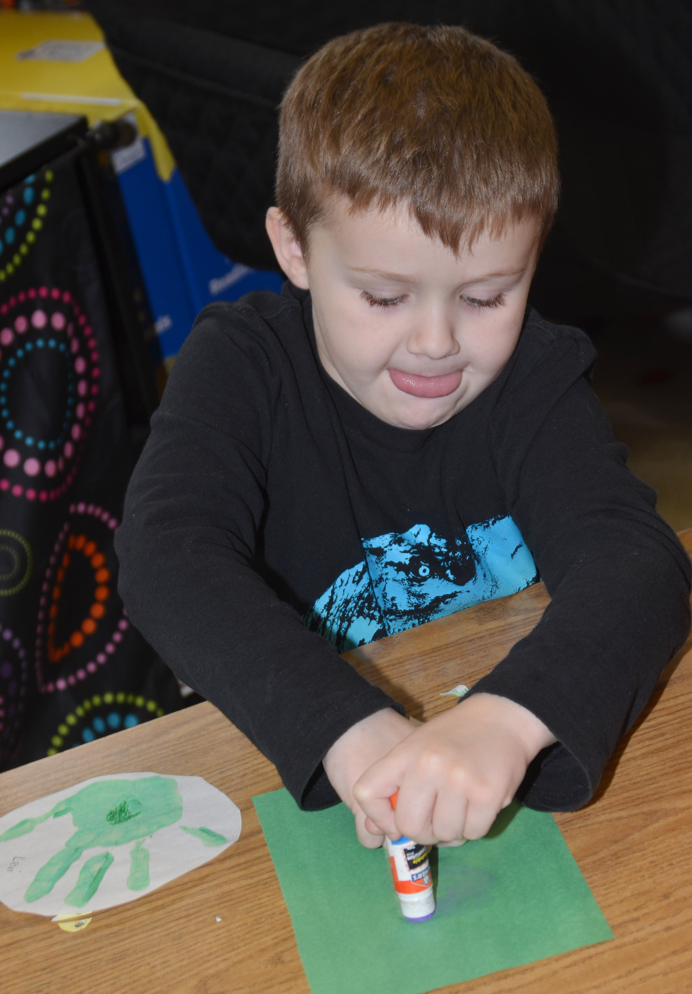 CES kindergartener Levi Dye glues his Grinch handprint.