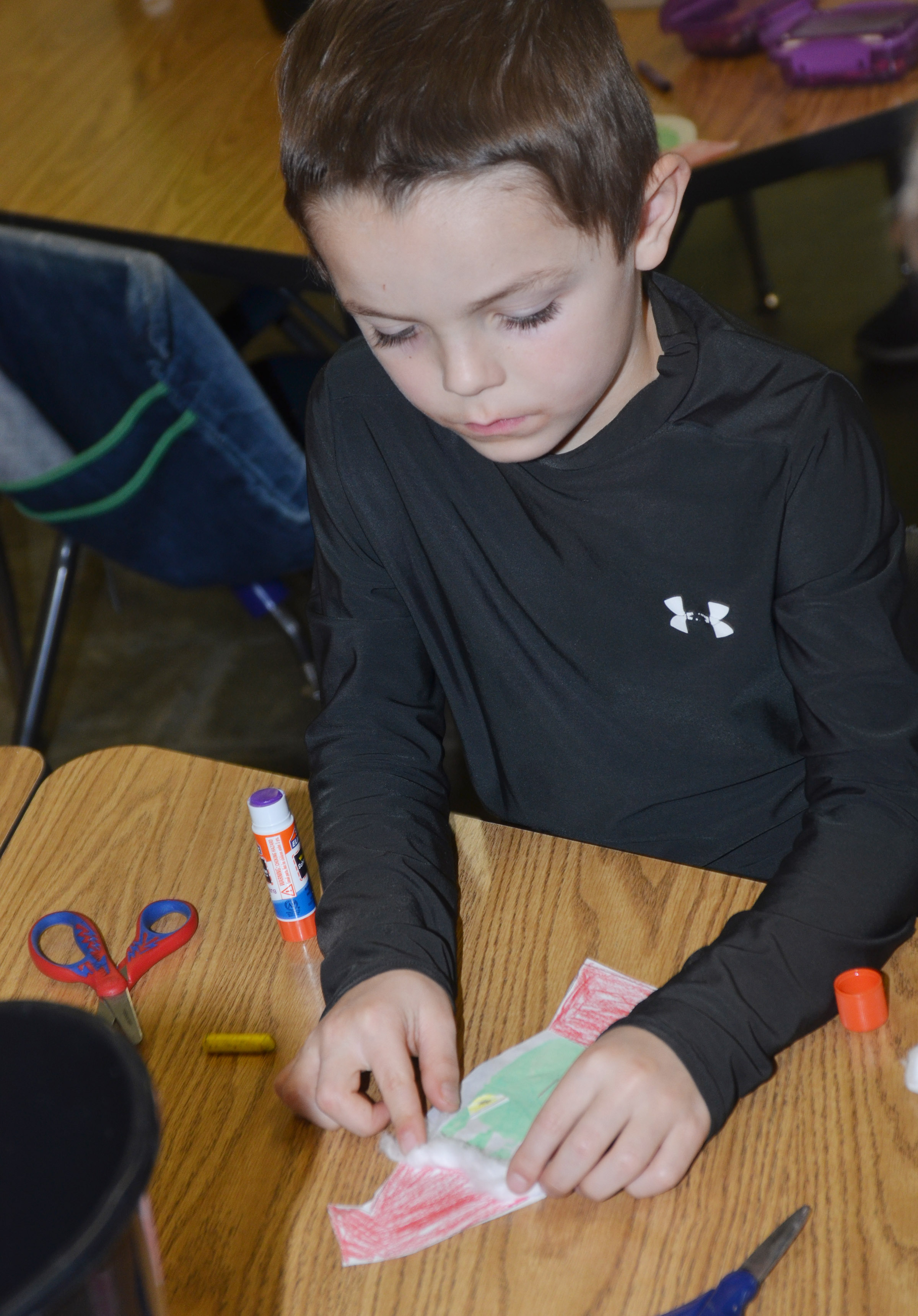 CES kindergartener Hayden Goff glues cotton on his Grinch.