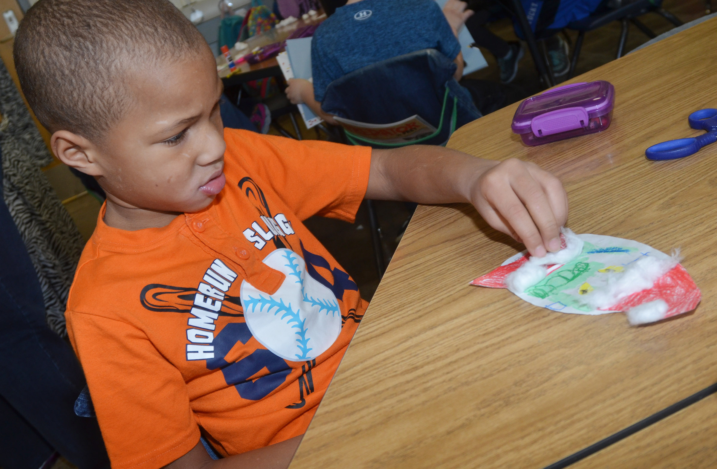 CES kindergartener Jamerius Miller glues cotton on his Grinch.