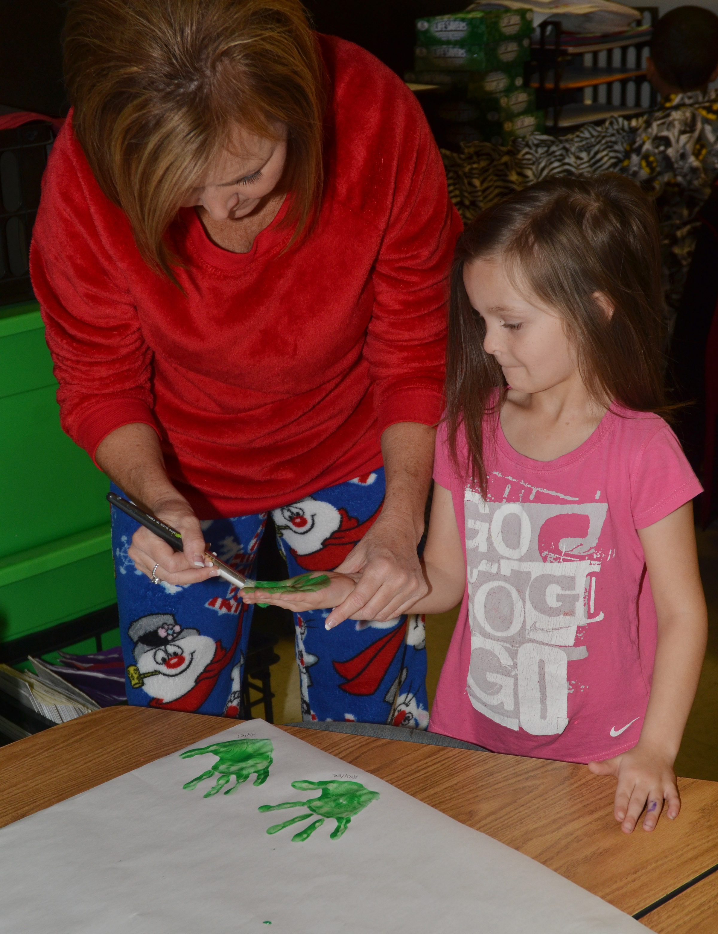 CES kindergartener teacher Lisa Wiseman paints Addison Perkins's hand.