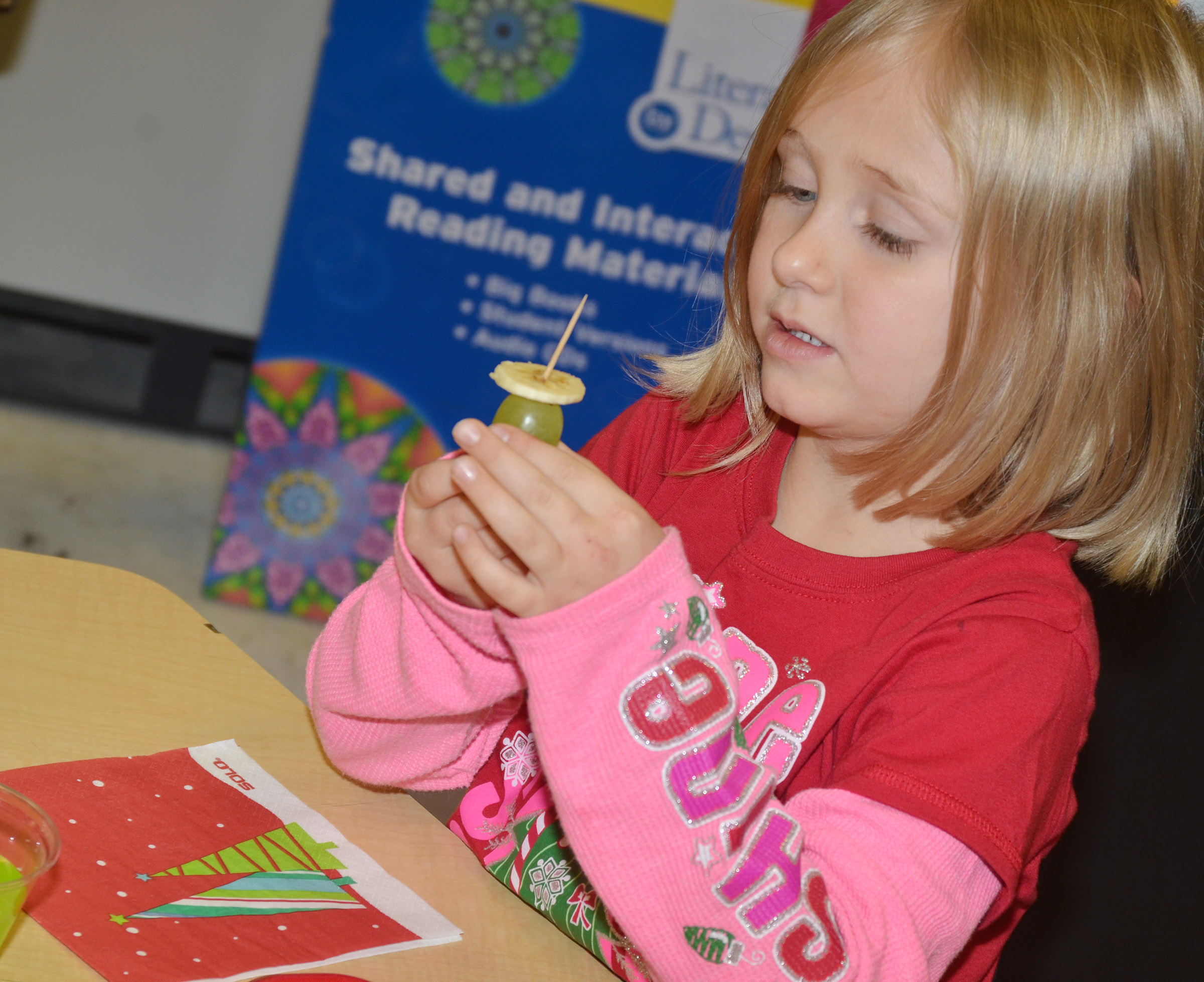 CES kindergartener LeeAnna Garvin makes her Grinch out of fruit.