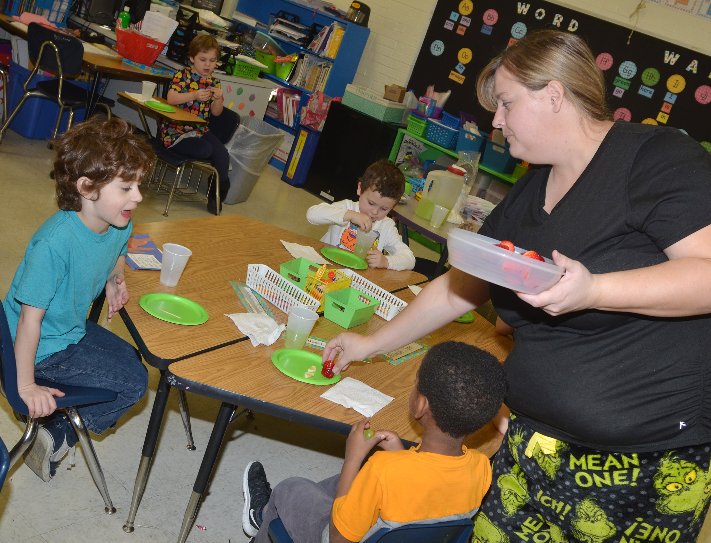 CES kindergarten teacher Kimberly Clark passes out fruit for her students to make their own Grinch snack.