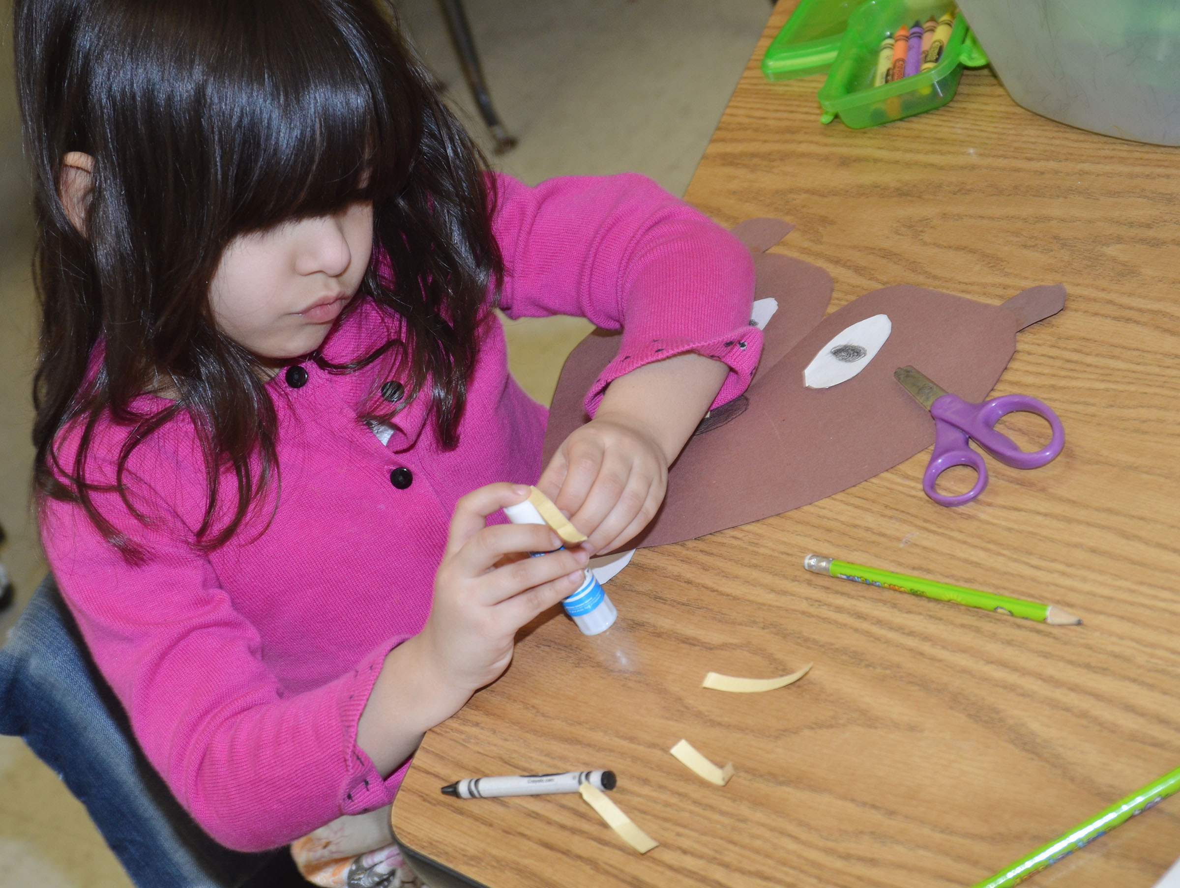 CES kindergartener Carol Moura glues her groundhog together.