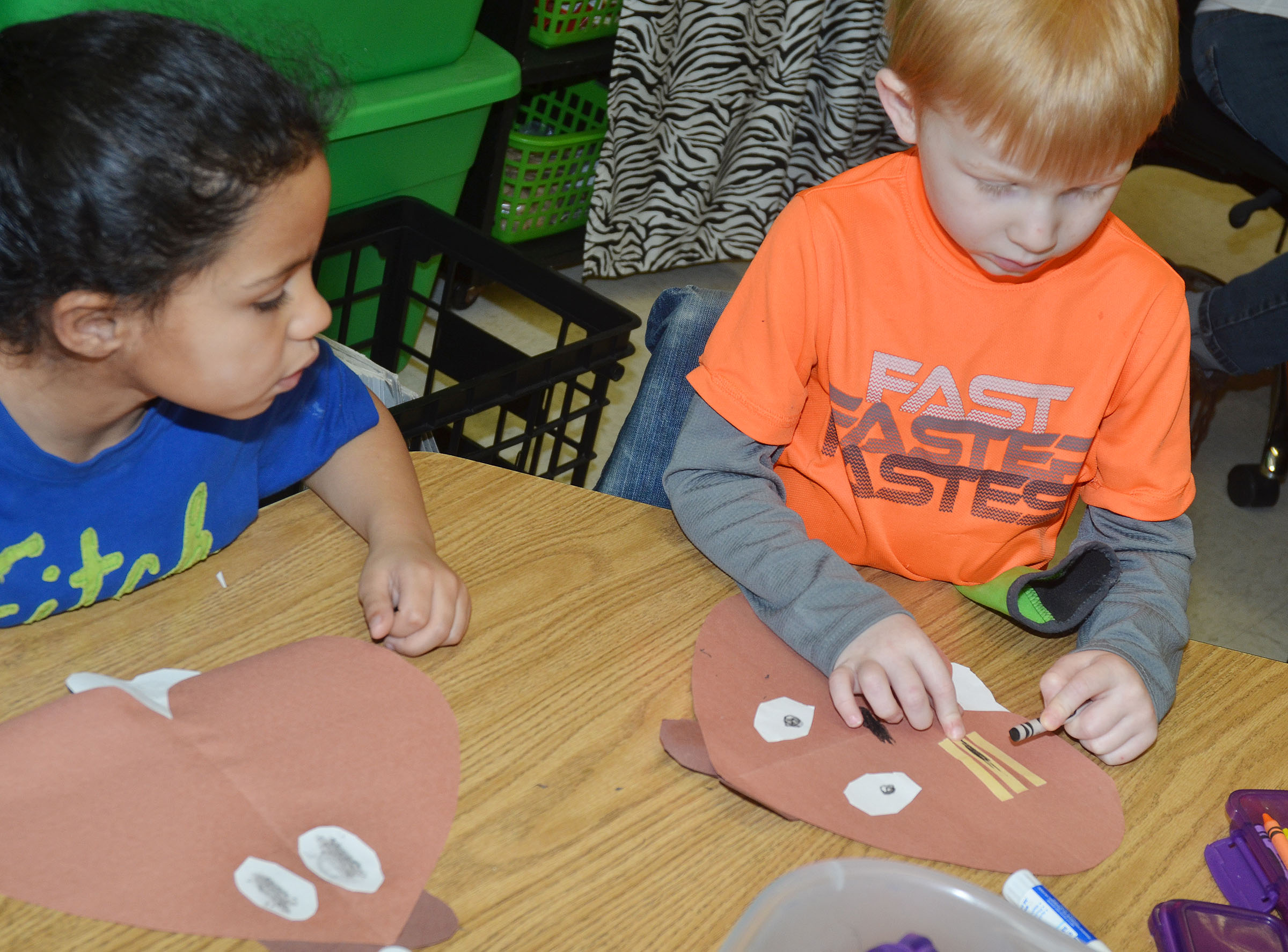 CES kindergarteners Jyra Welch, at left, and Jayden Maupin glue their groundhogs together.