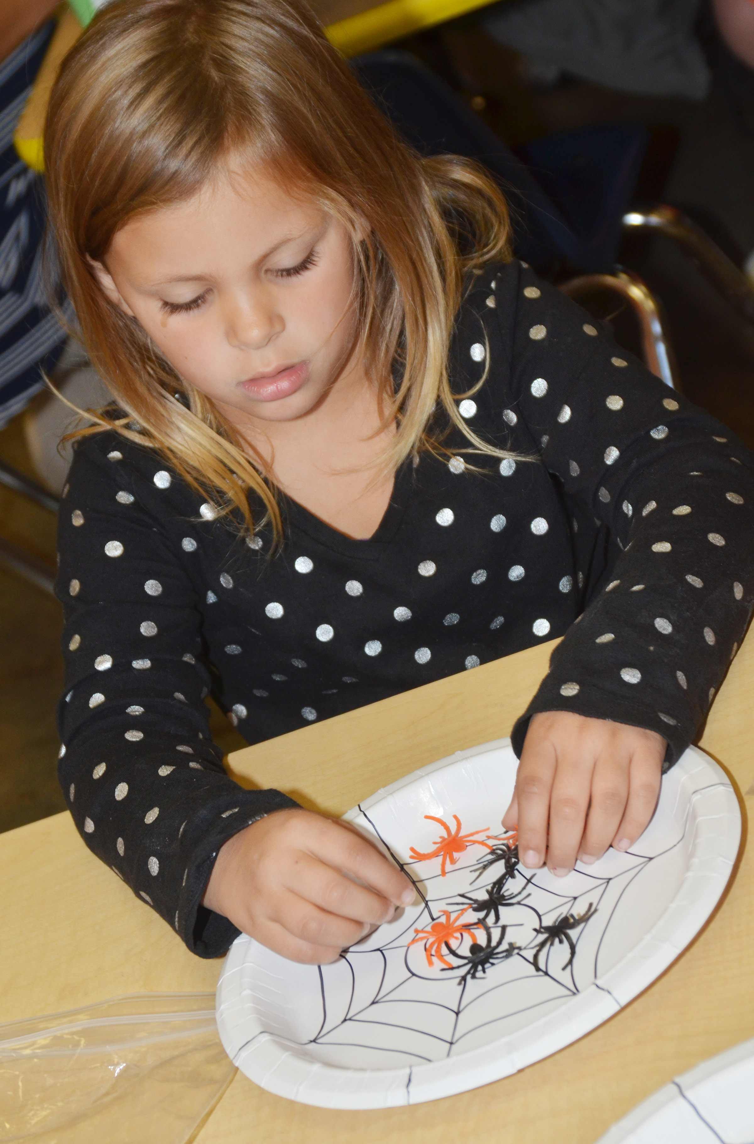 CES kindergartener Alaziah Smith counts with plastic spiders.