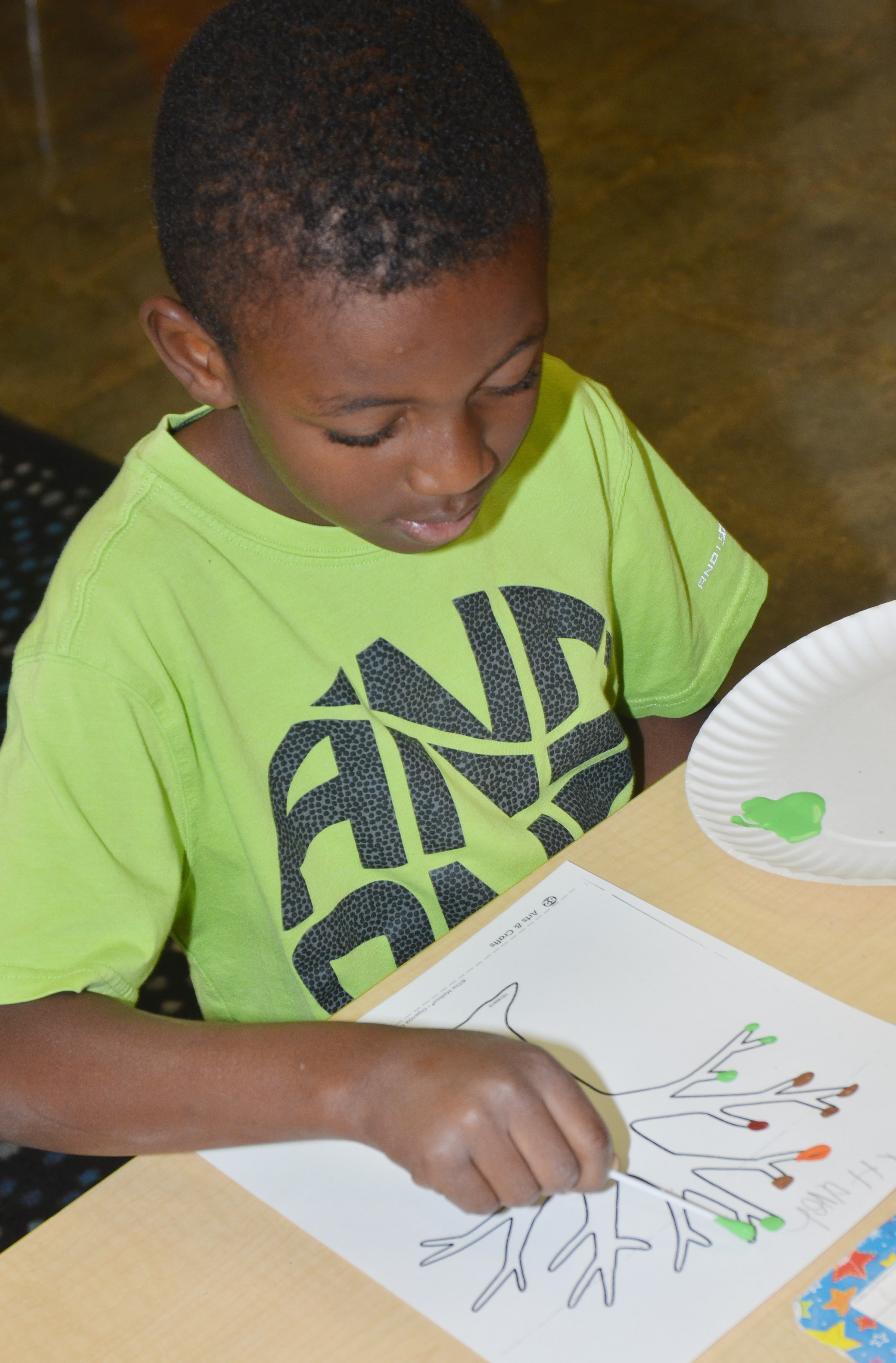 CES kindergartener Zyhaven Taylor paints leaves on his tree.